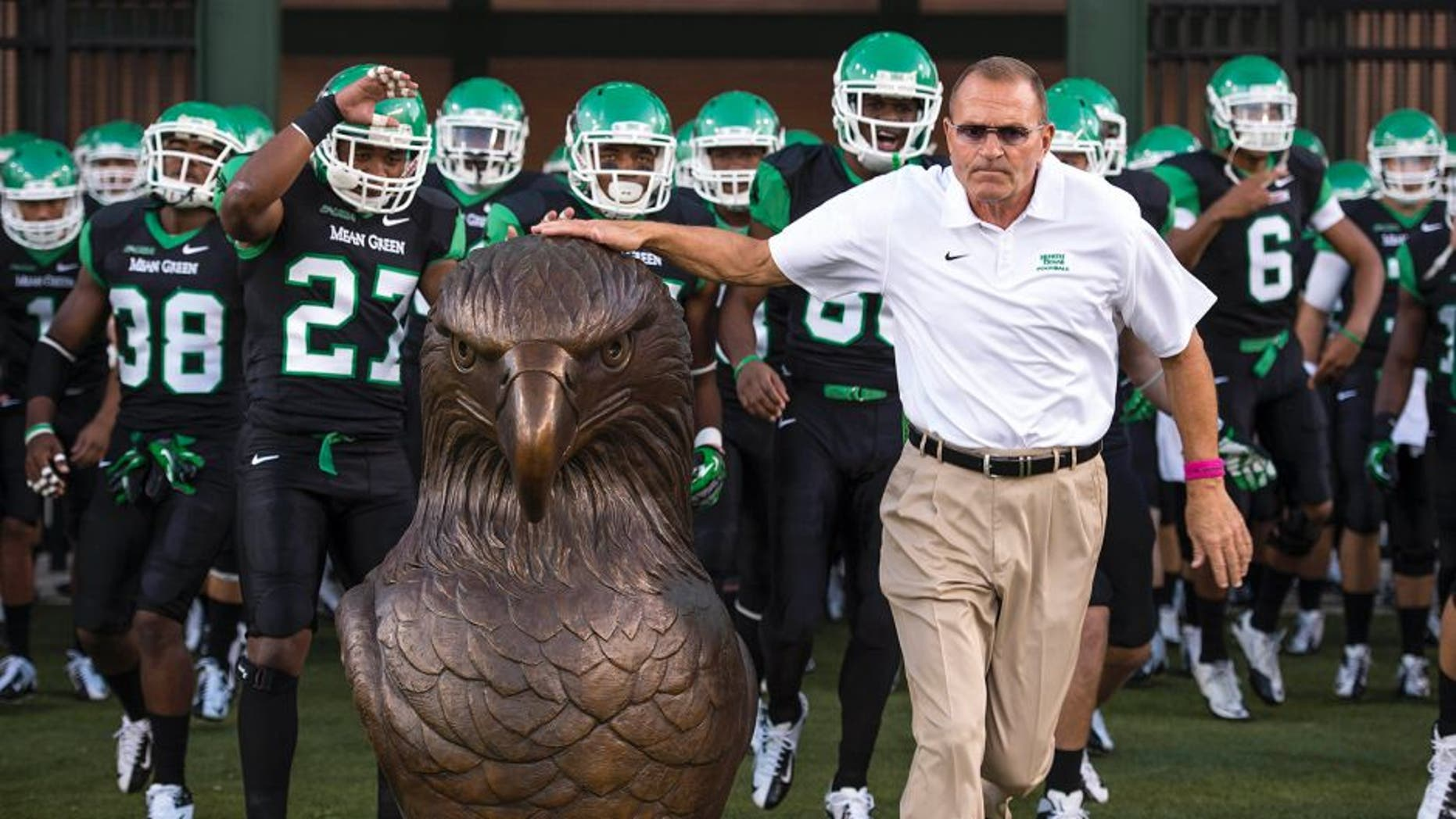Oct 31, 2013; Denton, TX, USA; North Texas Mean Green head coach Dan McCarney leads his team on the field to face the Rice Owls at Apogee Stadium. The Mean Green defeated the Owls 28-16. Mandatory Credit: Jerome Miron-USA TODAY Sports