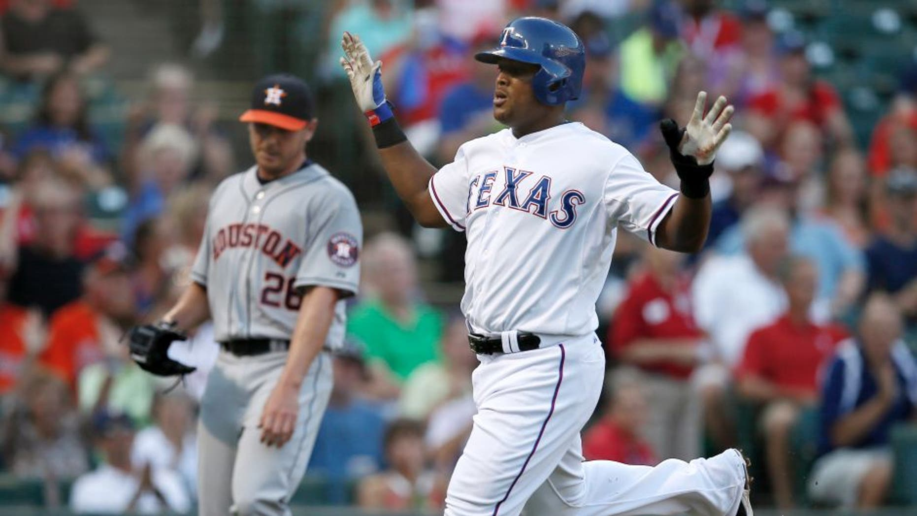 Texas Rangers' Adrian Beltre celebrates after crossing the plate, scoring on a Elvis Andrus single off of Houston Astros' Scott Kazmir, rear, in the first inning of a baseball game, Wednesday Aug. 5, 2015, in Arlington, Texas. (AP Photo/Tony Gutierrez)