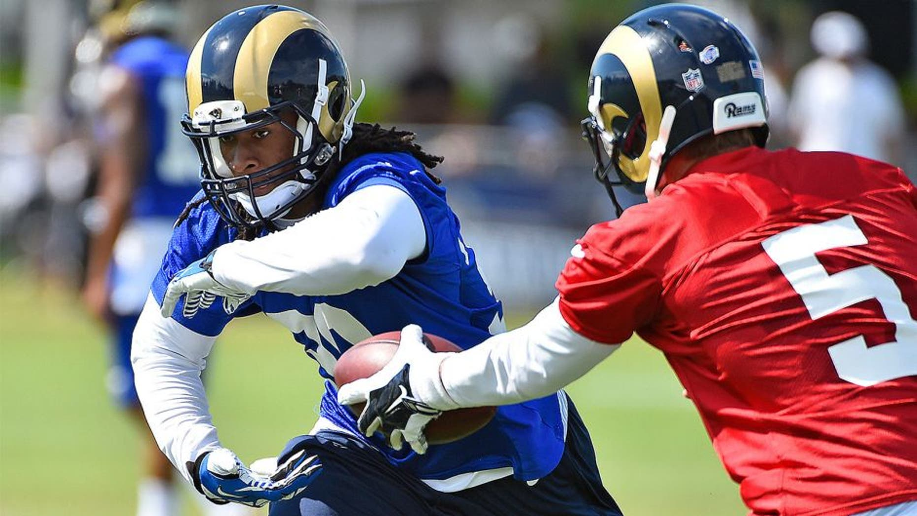 Aug 1, 2015; Earth City, MO, USA; St. Louis Rams quarterback Nick Foles (5) hands the ball to running back Todd Gurley (30) at Rams Park. Mandatory Credit: Jasen Vinlove-USA TODAY Sports