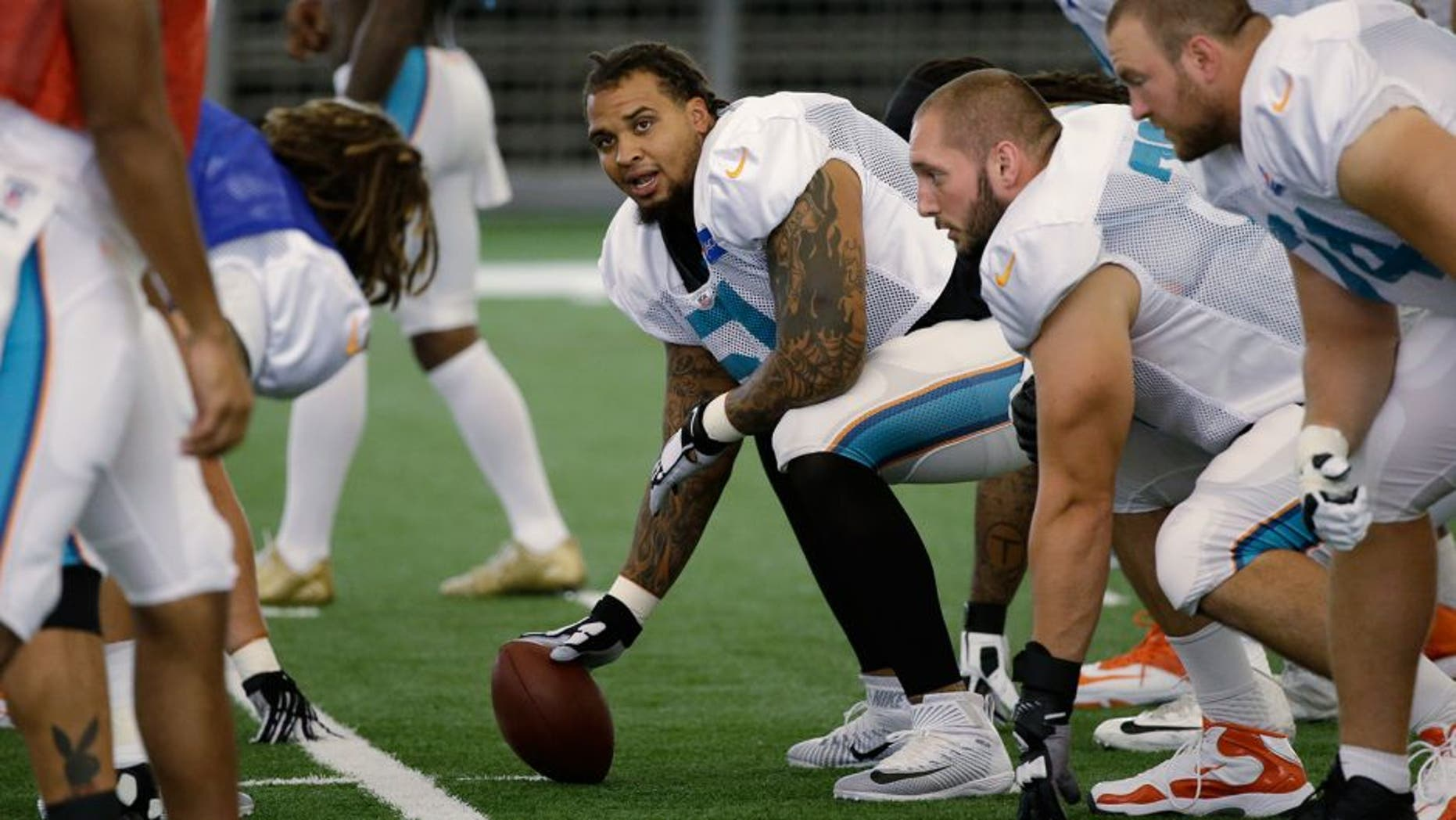 Miami Dolphins center Mike Pouncey, center, prepares to snap the ball at the teams NFL football training camp, Wednesday, Aug. 5, 2015, in Davie, Fla. (AP Photo/Wilfredo Lee)