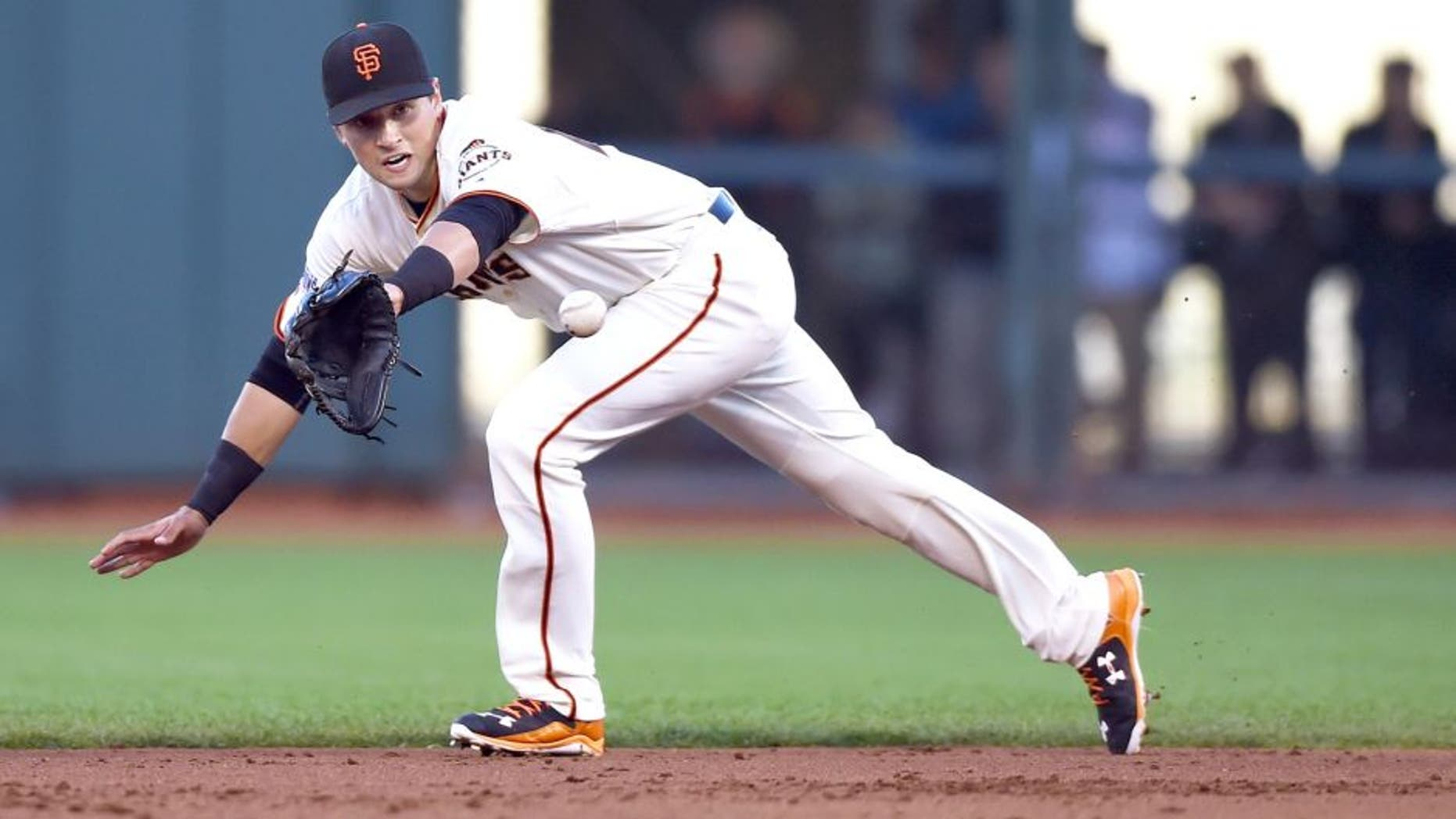 SAN FRANCISCO, CA - JULY 27: Joe Panik #12 of the San Francisco Giants goes up the middle to his backhand to take a hit away from Shane Peterson #35 of the Milwaukee Brewers in the top of the second inning at AT&T Park on July 27, 2015 in San Francisco, California. (Photo by Thearon W. Henderson/Getty Images)