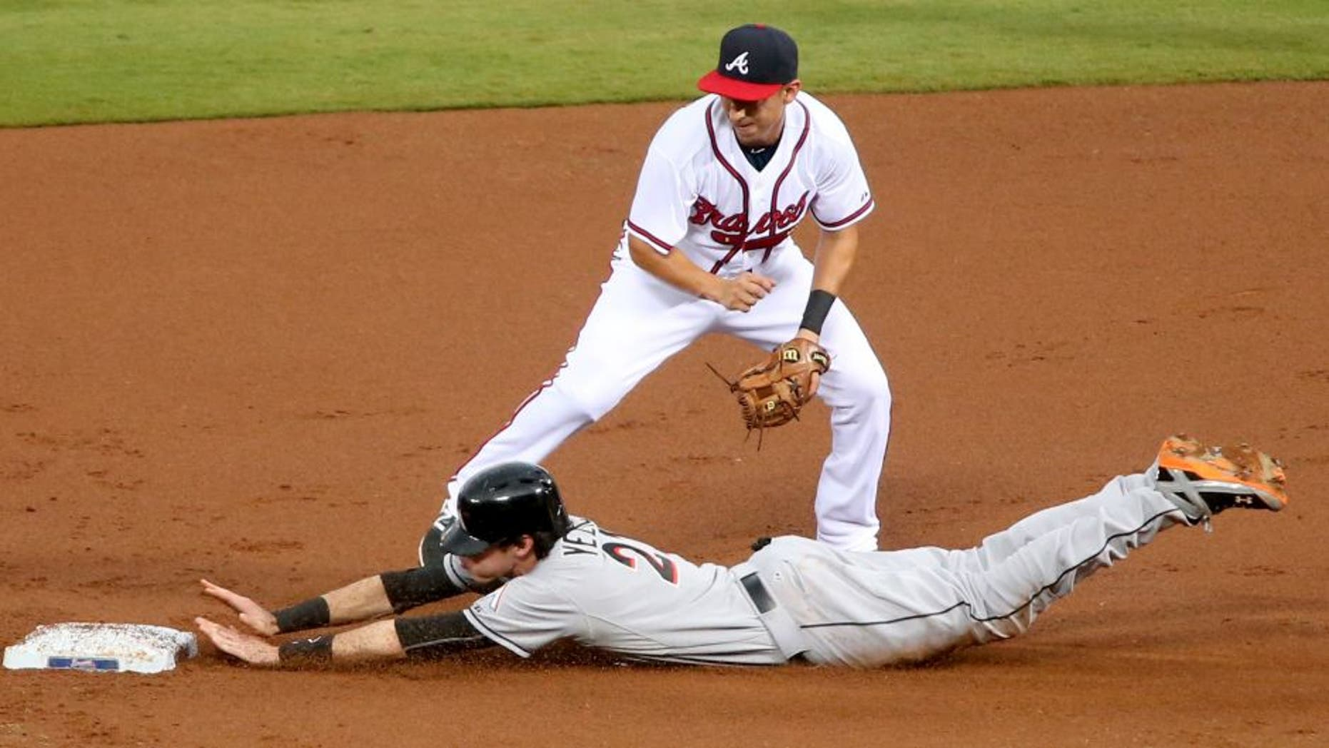 Aug 6, 2015; Atlanta, GA, USA; Miami Marlins left fielder Christian Yelich (21) steals second base ahead of the tag by Atlanta Braves shortstop Daniel Castro (11) in the first inning of their game at Turner Field. Mandatory Credit: Jason Getz-USA TODAY Sports