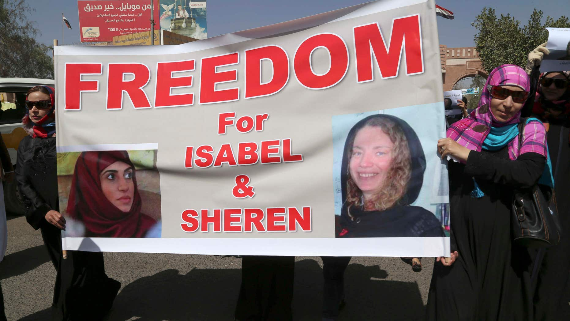 March 5, 2015: Yemeni activists hold a banner with pictures of kidnapped French Isabelle Prime, right, and her Yemeni colleague during a protest in Sanaa, Yemen.