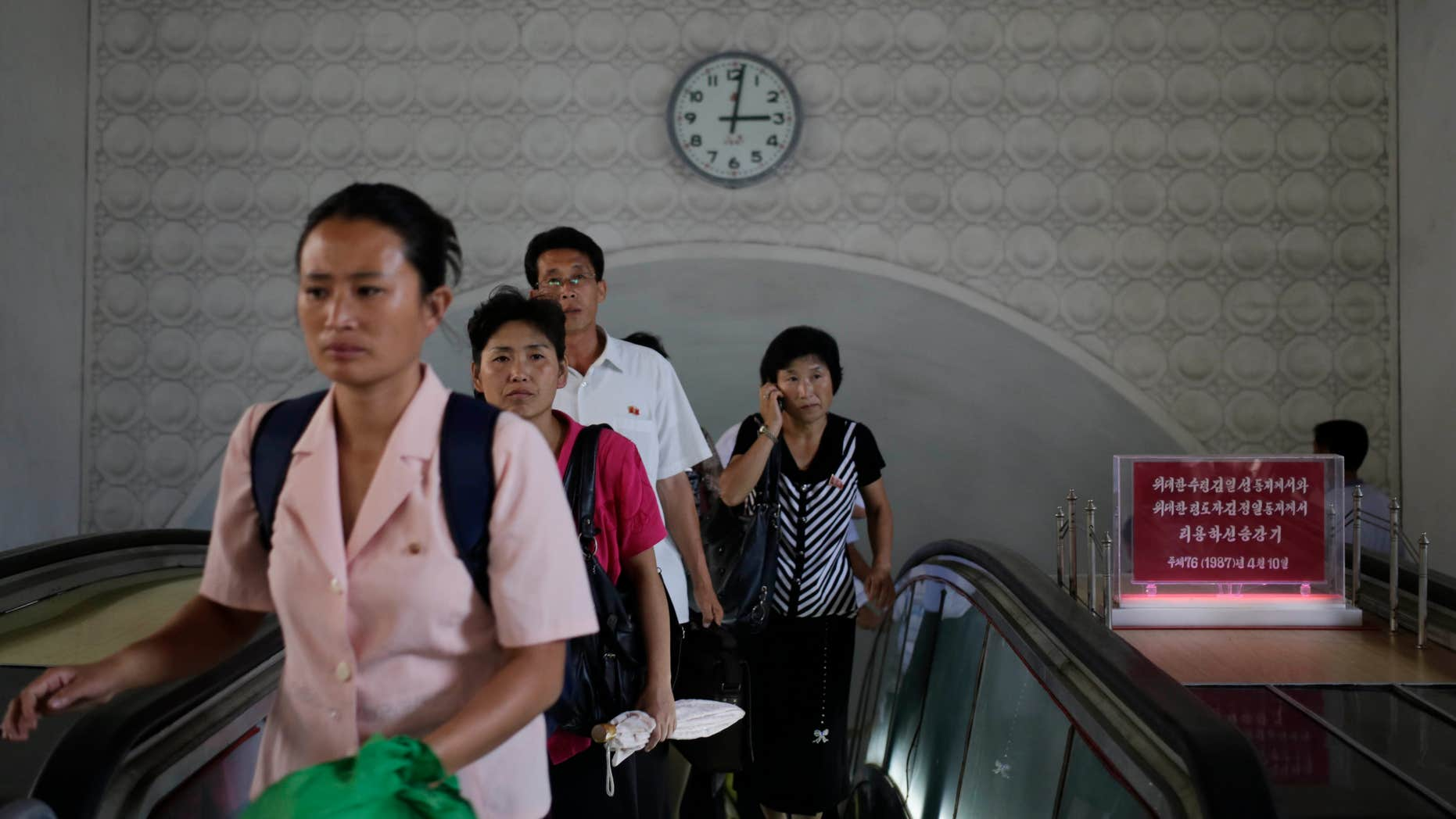 Sept. 1, 2014: A clock hangs on the wall as North Koreans leave an underground train station in Pyongyang, North Korea.