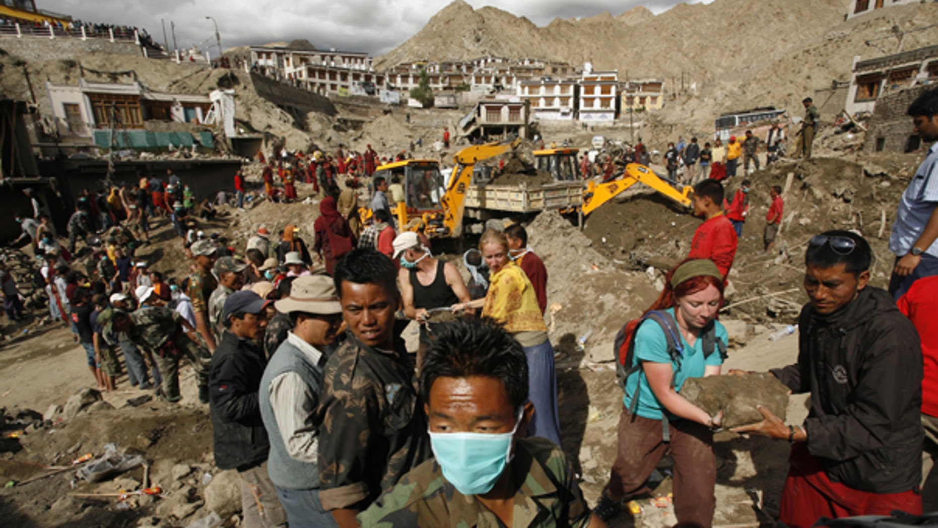 Aug. 7: Foreign tourists assist locals in removing debris from a flash flood-affected area of Leh, India. Authorities stepped up rescue efforts as the weather improved Saturday, a day after flash floods sent rivers of mud down desert mountainsides in Indian-controlled Kashmir, killing scores of people and injuring hundreds, officials said.