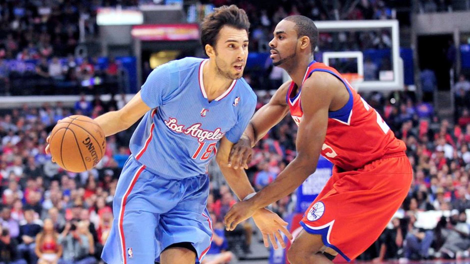 February 9, 2014; Los Angeles, CA, USA; Los Angeles Clippers shooting guard Sasha Vujacic (18) moves the ball against Philadelphia 76ers shooting guard Elliot Williams (25) during the second half at Staples Center. Mandatory Credit: Gary A. Vasquez-USA TODAY Sports