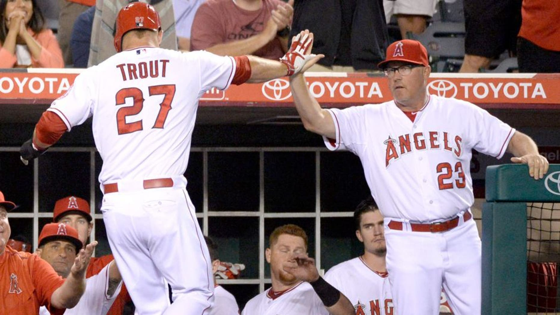 Aug 7, 2015; Anaheim, CA, USA; Los Angeles Angels pitching coach Mike Butcher (23) congratulates Los Angeles Angels center fielder Mike Trout (27) for scoring against the Baltimore Orioles during the fourth inning at Angel Stadium of Anaheim. Mandatory Credit: Richard Mackson-USA TODAY Sports