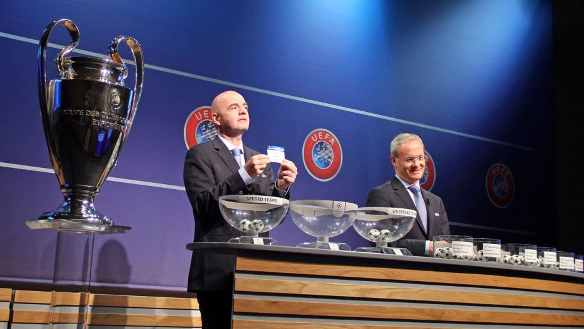 NYON, SWITZERLAND - JUNE 22: UEFA General Secretary Gianni Infantino (L) shows the lot of Lincoln Red Imps FC next to UEFA director of competitions Giorgio Marchetti (R) during the draw of the first two qualifying rounds of the UEFA Champions League 2015/16 at the UEFA Headquarters in Nyon, Switzerland on June 22, 2015. (Photo by Fatih Erel/Anadolu Agency/Getty Images)