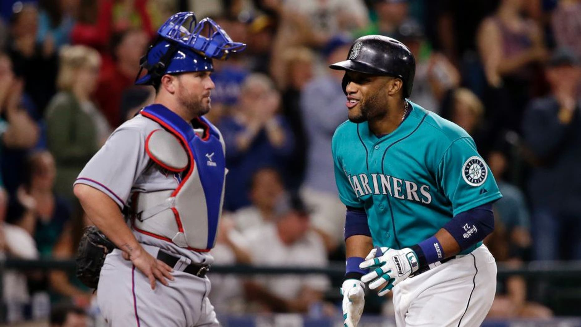 Seattle Mariners' Robinson Cano, right, smiles as he scores on his home run as Texas Rangers catcher Bobby Wilson waits during the sixth inning of a baseball game Friday, Aug. 7, 2015, in Seattle. (AP Photo/Elaine Thompson)