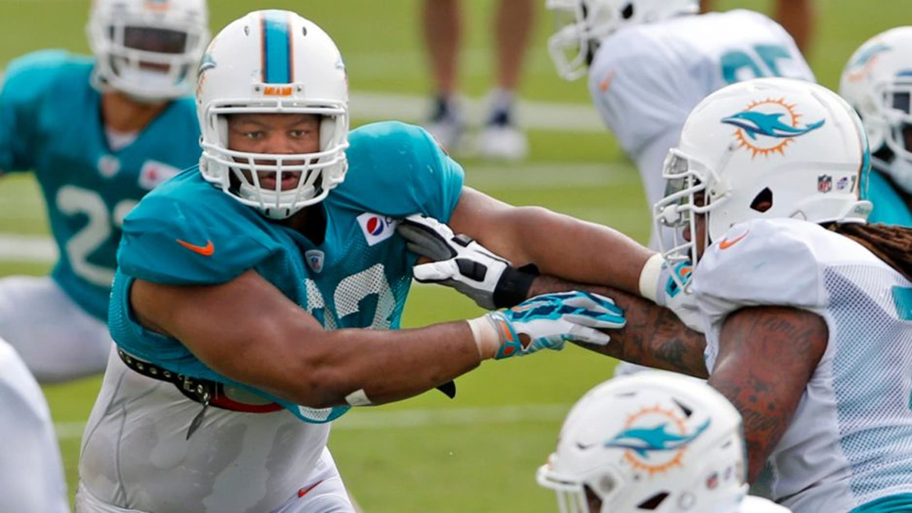 Miami Dolphins defensive tackle Ndamukong Suh (93) runs drills during NFL training camp, Saturday, Aug. 1, 2015 at Nova Southeastern University in Davie, Fla. (Al Diaz/The Miami Herald via AP) MAGS OUT; MANDATORY CREDIT