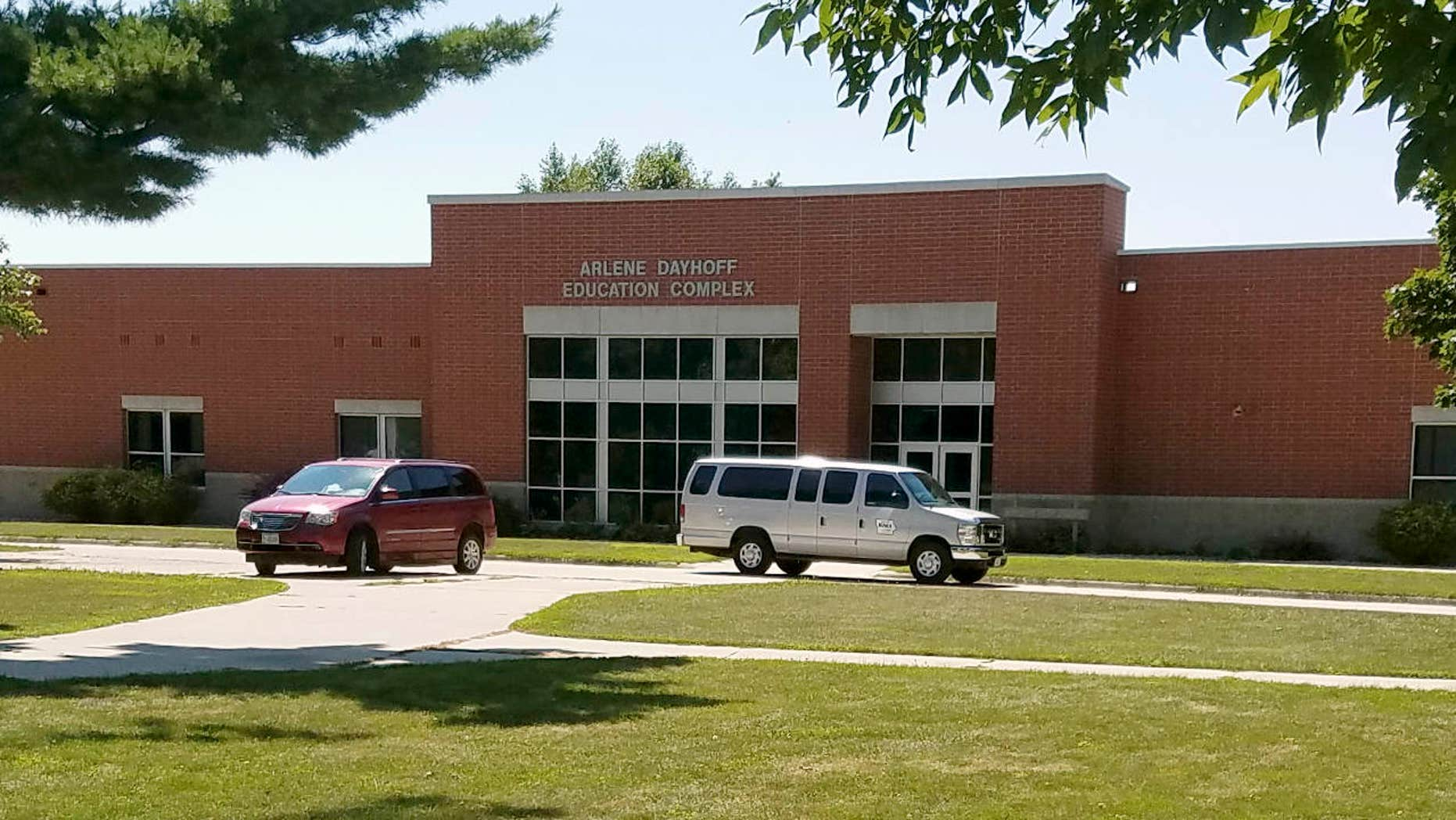 In this photo provided by the State of Iowa, vehicles are parked out the entrance to the Arlene Dayhoff Education Complex at the Boys State Training School in Eldora, Iowa, Monday, Aug. 7, 2017.
