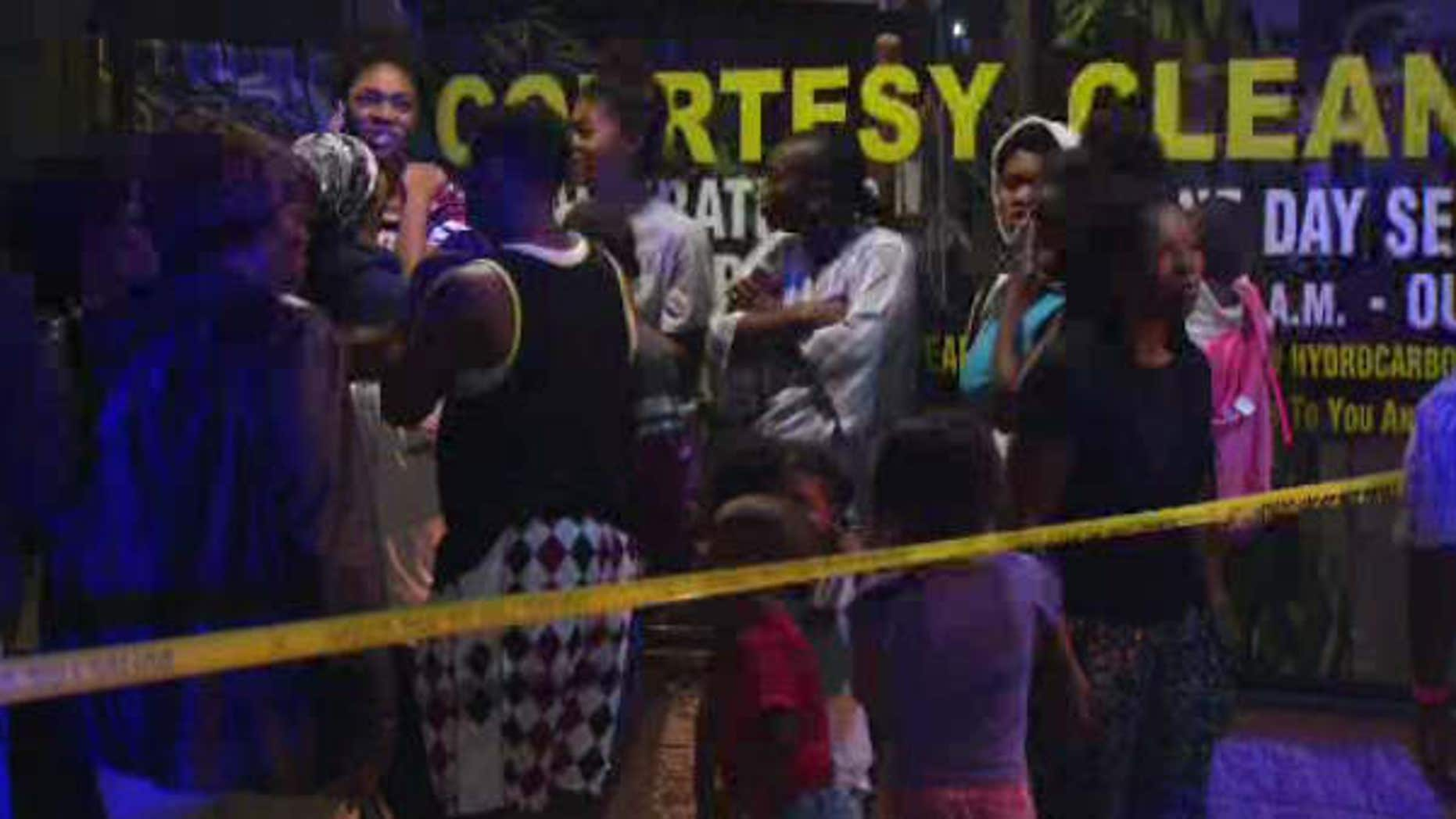 Aug. 7, 2015: In this image made from a video provided by KNBC-TV, relatives of a suspected attacker arrive at the scene after a fatal police shooting in Long Beach, Calif.
