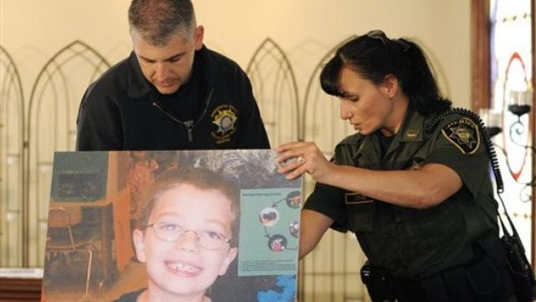 June 7: Officers Mary Lindstrand, right, of Multnomah County and Dave Thompson of Washington County set up a photo of missing 7-year-old Kyron Horman, prior to a news conference at Brooks Hill Historic church across from Skyline Elementary School in Portland, Ore.