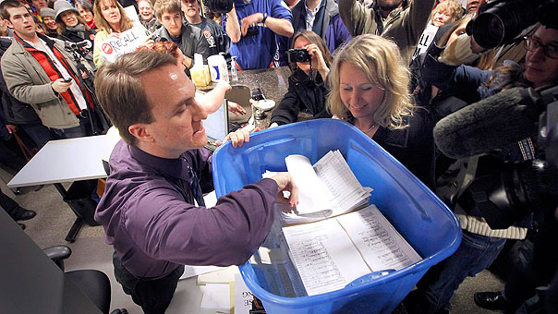 In this April 1, 2011 file photo, David Buerger, an elections specialist with the Wisconsin Government Accountability Board, inspects recall petitions filed against Sen. Dan Kapanke, R-LaCrosse, in his Madison, Wis. office.