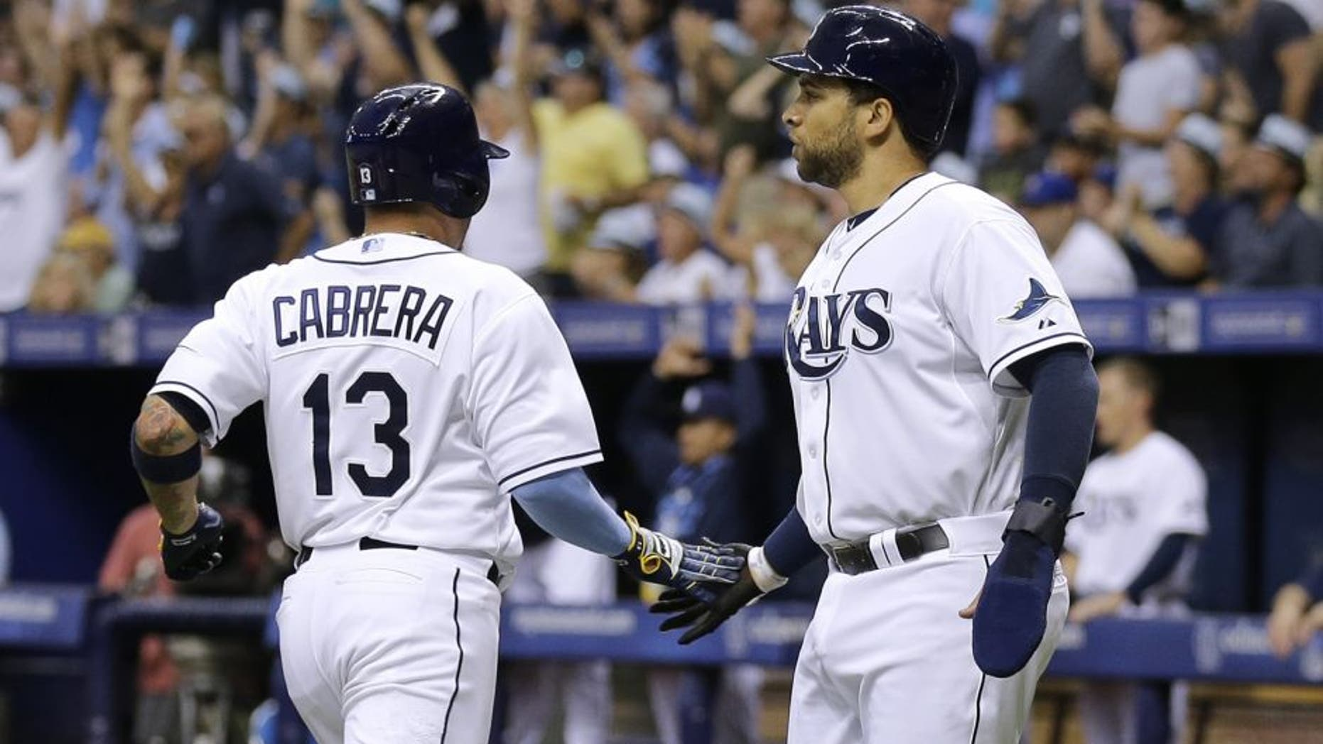 Tampa Bay Rays' James Loney and Asdrubal Cabrera (13) celebrate after scoring on a two-run single by Kevin Kiermaier off New York Mets starting pitcher Noah Syndergaard during the first inning of an interleague baseball game Saturday, Aug. 8, 2015, in St. Petersburg, Fla. (AP Photo/Chris O'Meara)