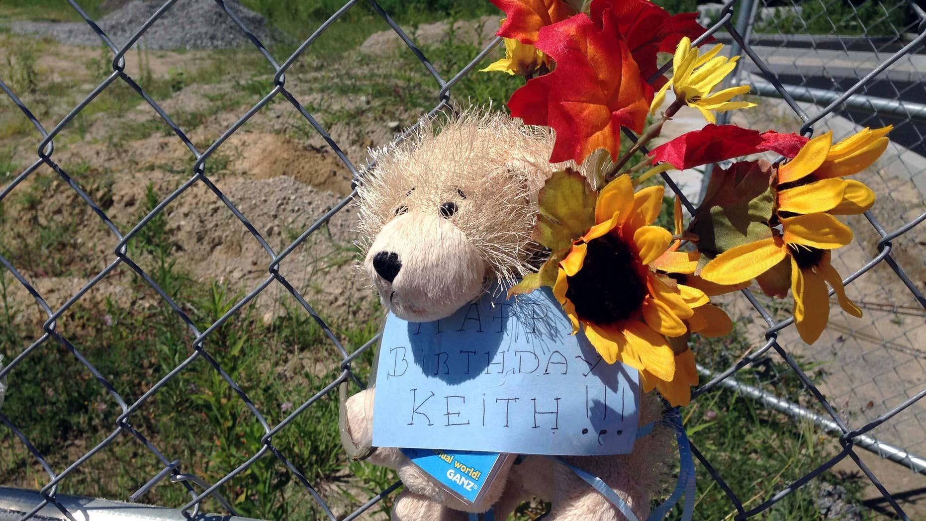 In this Thursday, Aug. 4, 2016 photo, a stuffed animal hangs from a chain link fence that surrounds the site of a 2003 nightclub fire that killed 100 people in West Warwick, R.I.