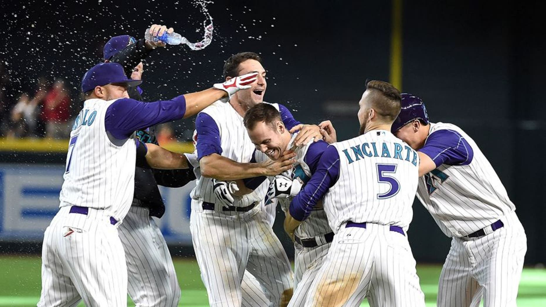 PHOENIX, AZ - AUGUST 09: Chris Owings #16 of the Arizona Diamondbacks celebrates with teammates after hitting a walk off single in the tenth inning against the Cincinnati Reds at Chase Field on August 9, 2015 in Phoenix, Arizona. Arizona won 4-3. (Photo by Norm Hall/Getty Images)