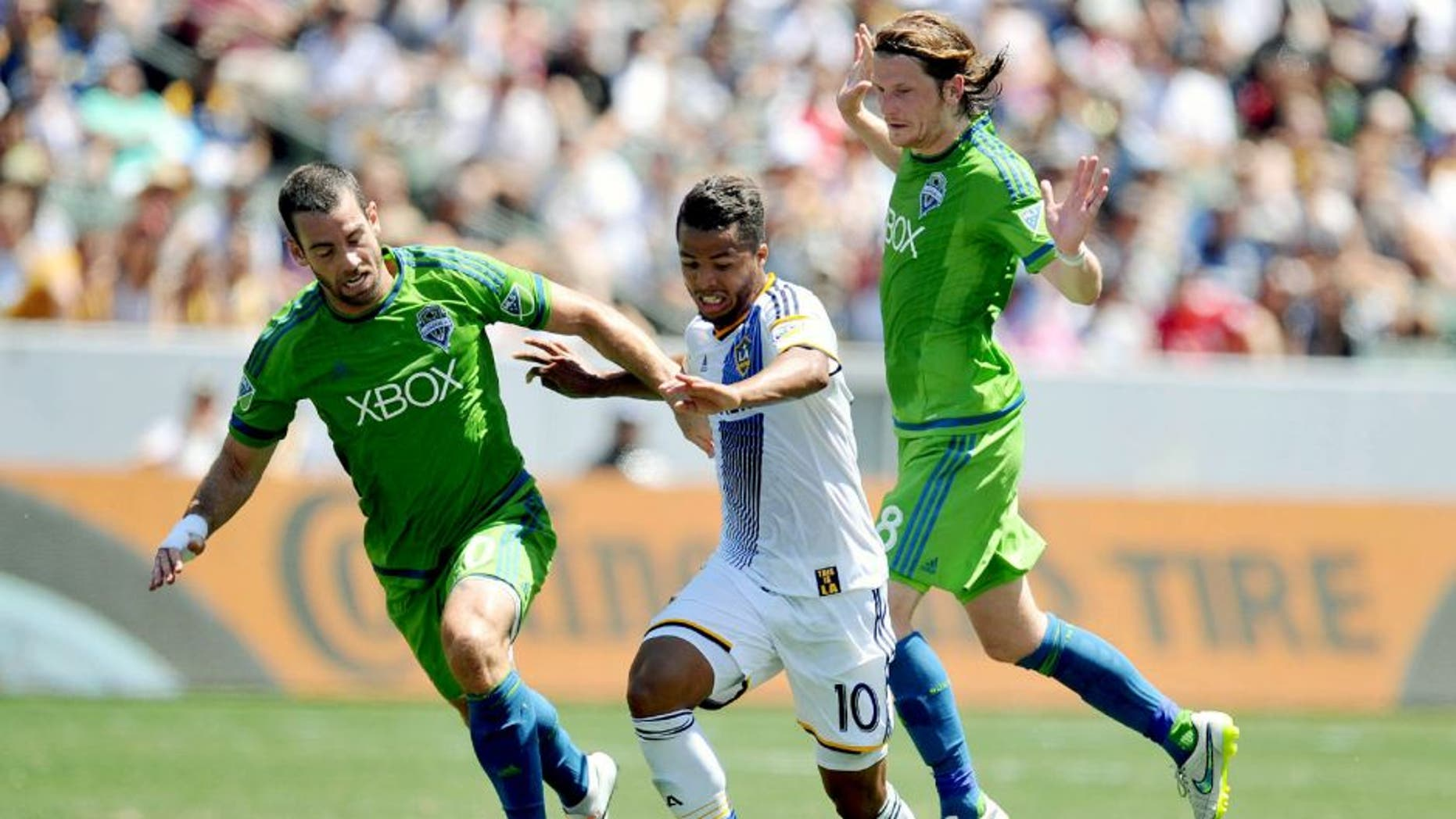 August 9, 2015; Carson, CA, USA; Los Angeles Galaxy midfielder/forward Giovani Dos Santos (10) moves the ball against Seattle Sounders defender Zach Scott (20) and midfielder Erik Friberg (28) during the first half at StubHub Center. Mandatory Credit: Gary A. Vasquez-USA TODAY Sports