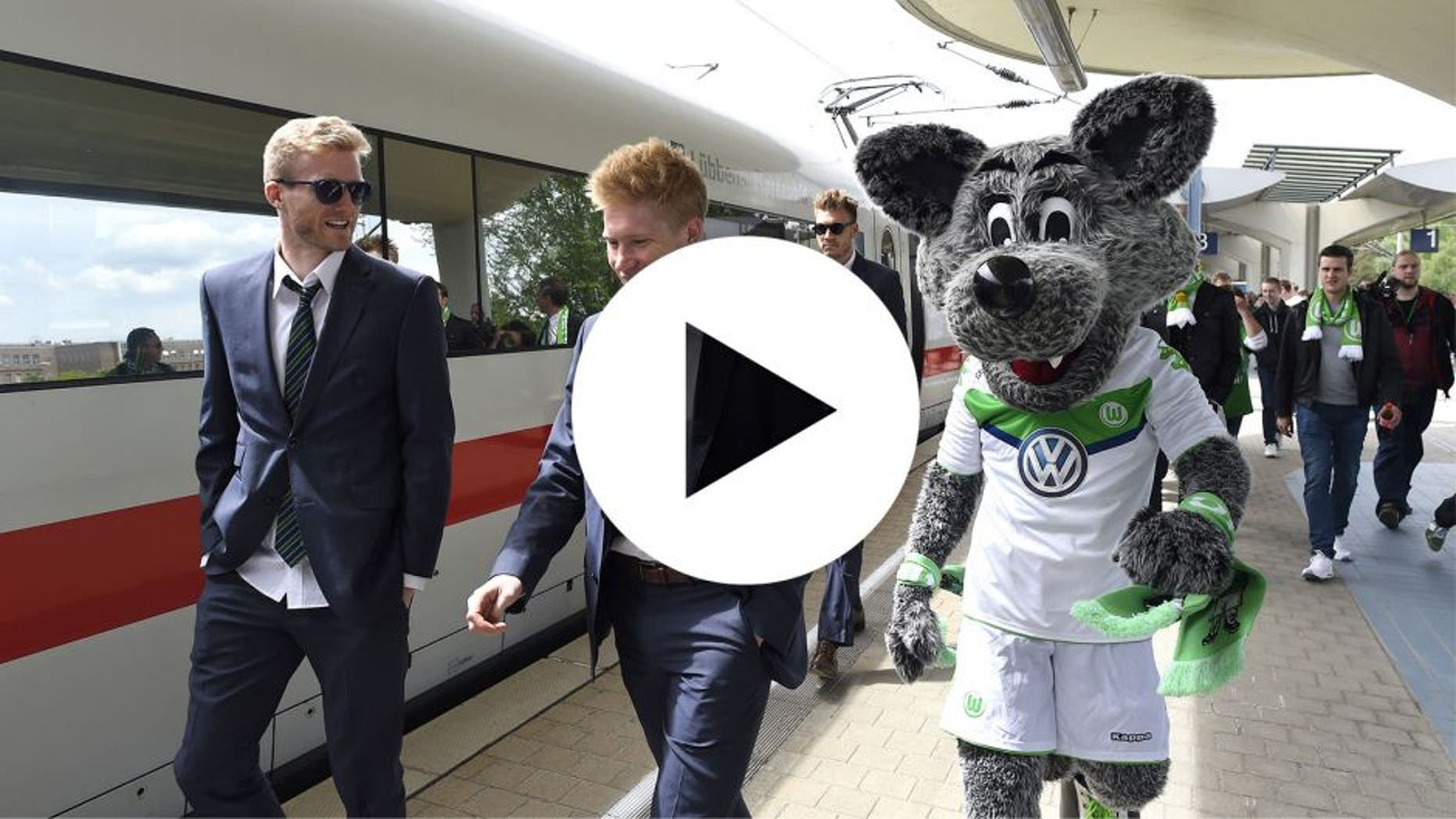 Wolfsburg's striker Andre Schuerrle (L) walks with Wolfsburg's Belgian midfielder Kevin De Bruyne and Wolfsburg's mascot on arrival at the main station in Wolfsburg, central Germany on May 31, 2015, after the German Cup DFB Pokal final football match between BVB Borussia Dortmund and VfL Wolfsburg on May 30 in Berlin. Wolfsburg won the match 1-3. AFP PHOTO / TOBIAS SCHWARZ (Photo credit should read TOBIAS SCHWARZ/AFP/Getty Images)