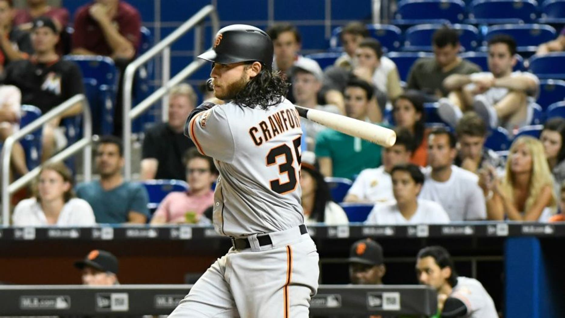 MIAMI, FL - AUGUST 08: Brandon Crawford #35 of the San Francisco Giants hit a base hit in the top of the 14th inning to score Brandon Belt #9 against the Miami Marlins at Marlins Park on August 8, 2016 in Miami, Florida. (Photo by Eric Espada/Getty Images) *** Local Caption *** Brandon Crawford