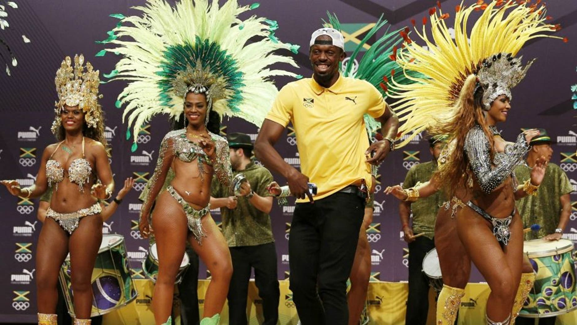 TOPSHOT - Usain Bolt (C) dances samba during a Jamaican Olympic Association and Puma press conference at the Cidade Das Artes in Rio de Janeiro on August 8, 2016. / AFP / Adrian DENNIS (Photo credit should read ADRIAN DENNIS/AFP/Getty Images)