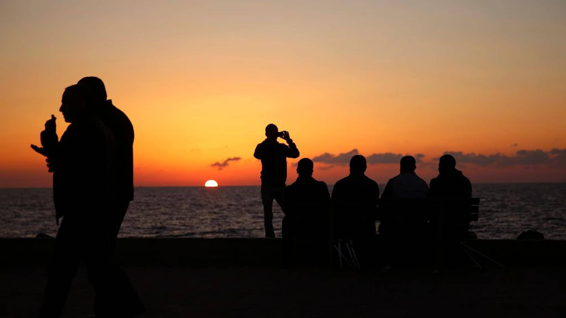 Palestinians sit on a chair during the sunset, at the Gaza port, in Gaza City, Monday, Dec. 12, 2016. The harbor is one of the few open public spaces in this densely populated city. (AP Photo/Hatem Moussa)