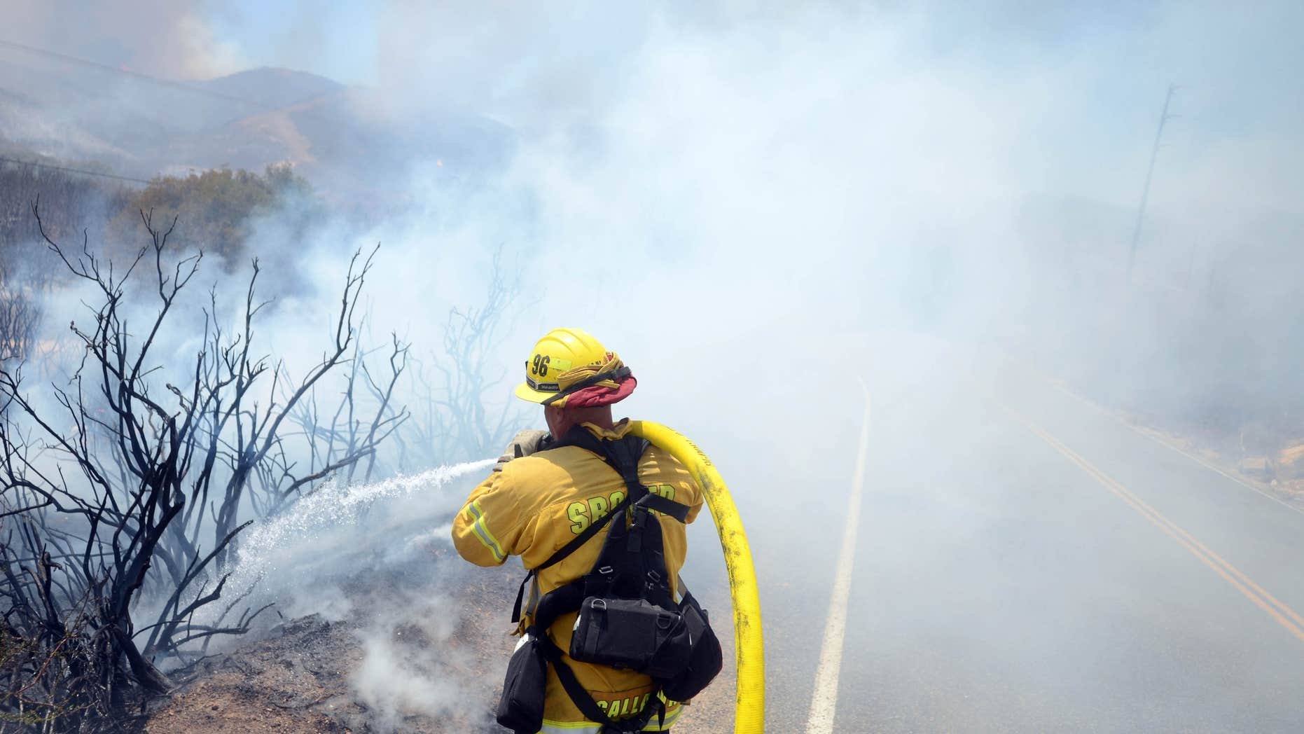 Aug. 8, 2016: San Bernardino County Firefighter Mike Callaway battles flames from a wildfire in Hesperia, Calif.
