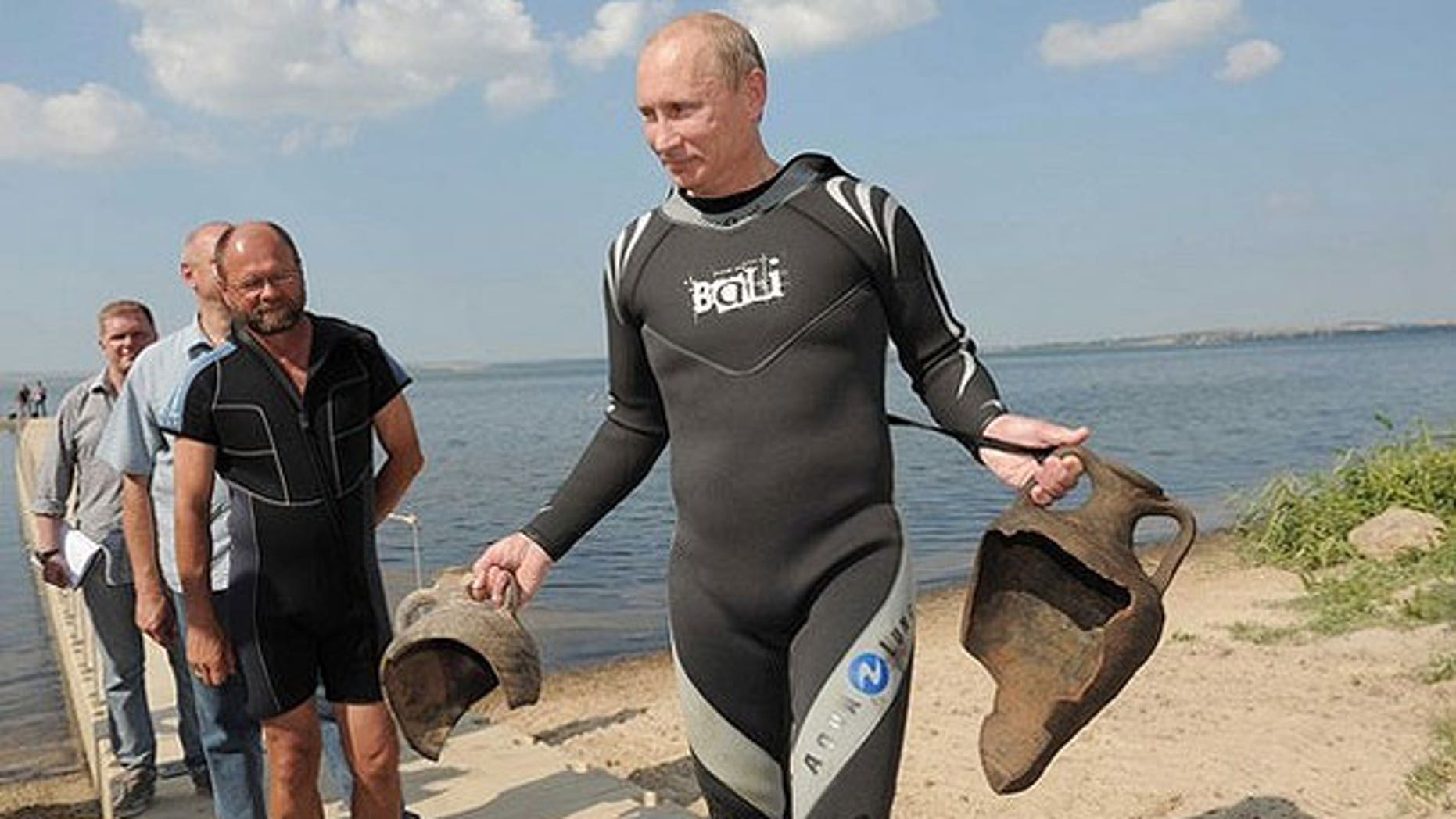 Aug. 10: Russian Prime Minister Vladimir Putin carries artifacts he recovered whilst diving at an archaeological site off the Taman peninsular in southern Russia.