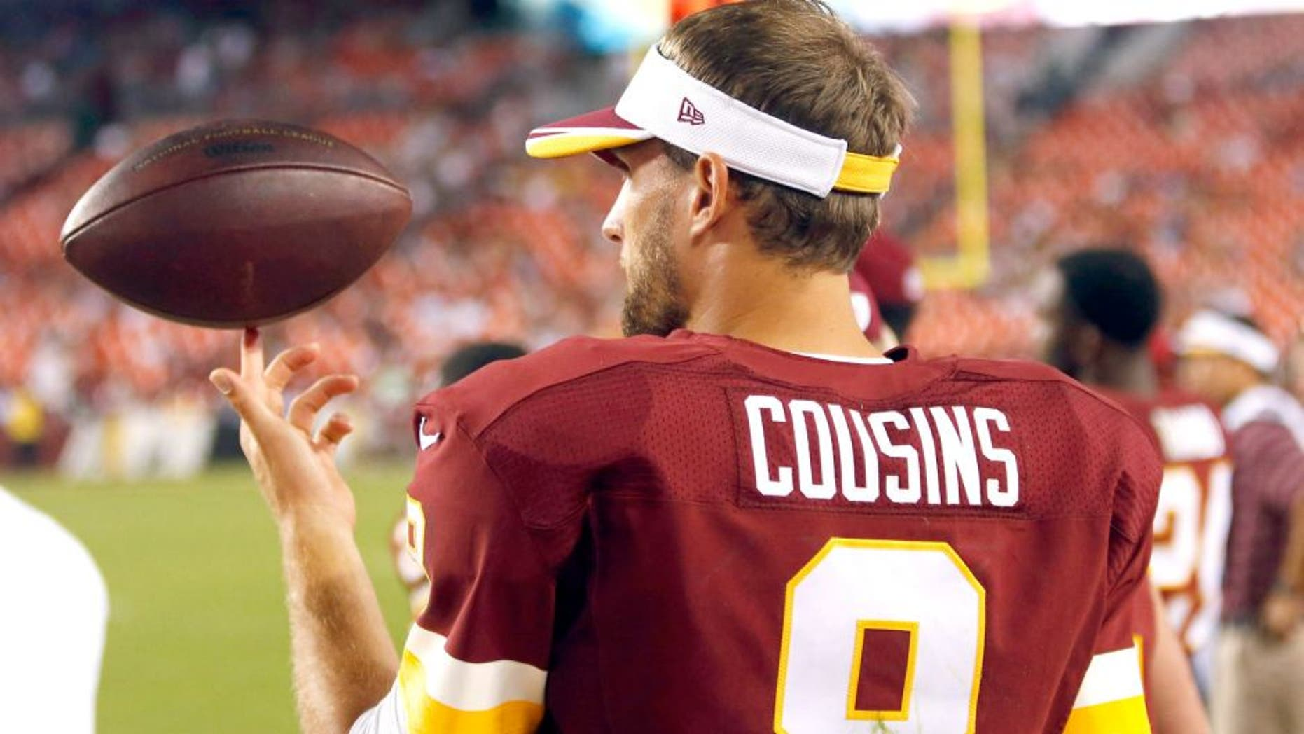 Aug 7, 2014; Landover, MD, USA; Washington Redskins quarterback Kirk Cousins (8) spins a ball on his finger on the sidelines against the New England Patriots in the third quarter at FedEx Field. The Redskins won 23-6. Mandatory Credit: Geoff Burke-USA TODAY Sports