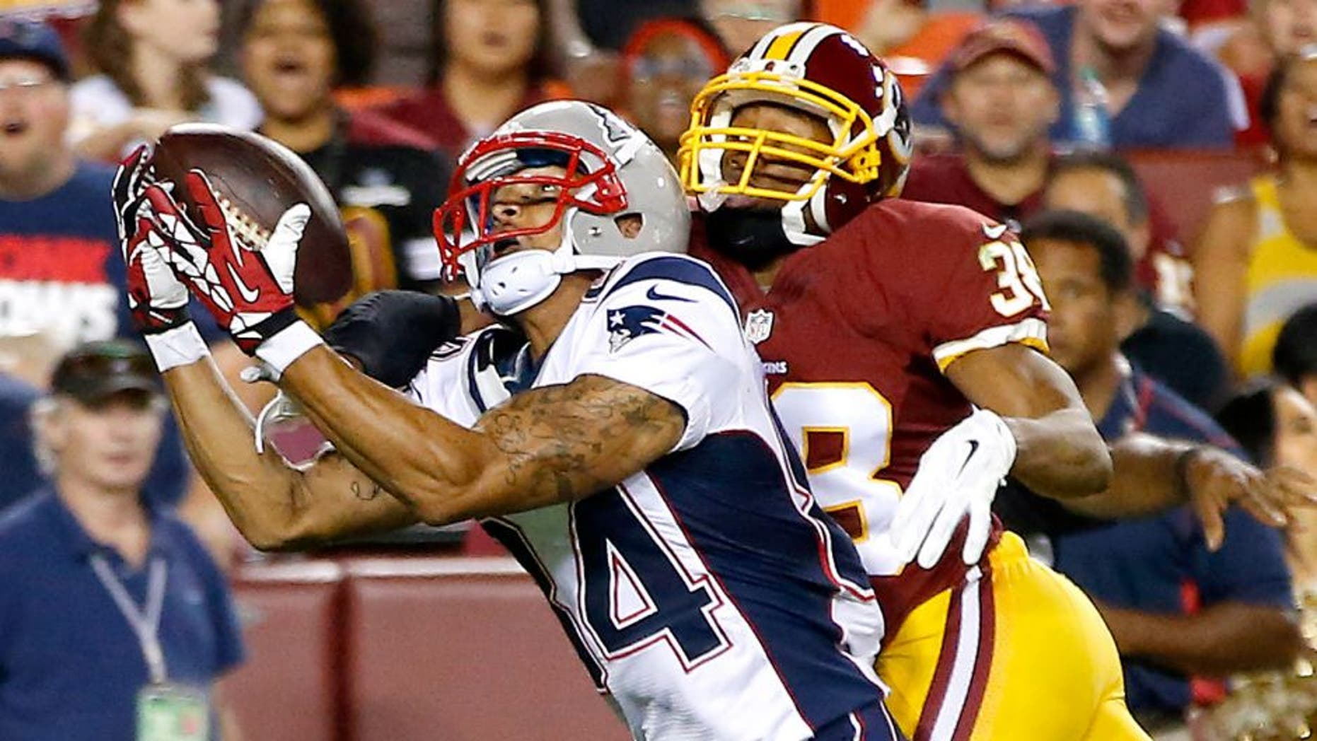 Aug 7, 2014; Landover, MD, USA; New England Patriots wide receiver Brian Tyms attempts to catch the ball as Washington Redskins defensive back Chase Minnifield (38) defends in the third quarter during a preseason game at FedEx Field. The Redskins won 23-6. Mandatory Credit: Geoff Burke-USA TODAY Sports
