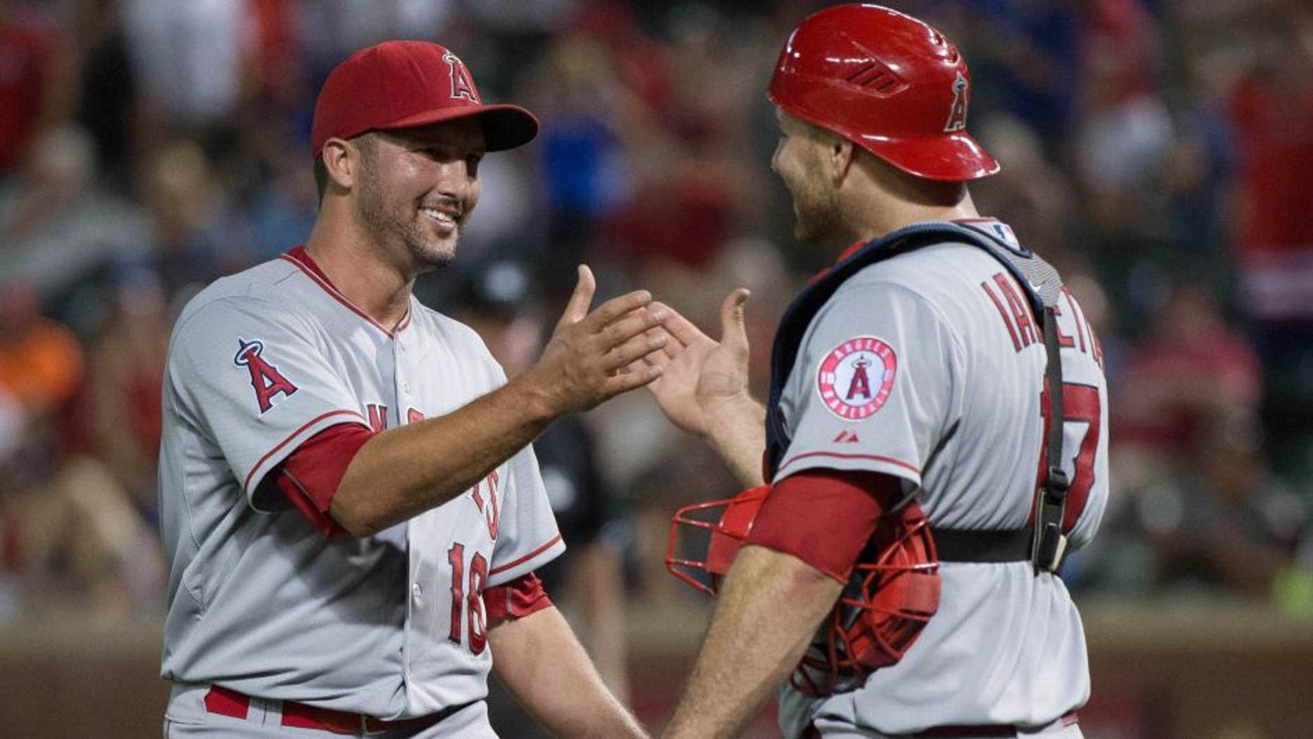 Jul 5, 2015; Arlington, TX, USA; Los Angeles Angels relief pitcher Huston Street (16) and catcher Chris Iannetta (17) celebrate the win over the Texas Rangers at Globe Life Park in Arlington. The Angels defeated the Rangers 12-6. Mandatory Credit: Jerome Miron-USA TODAY Sports