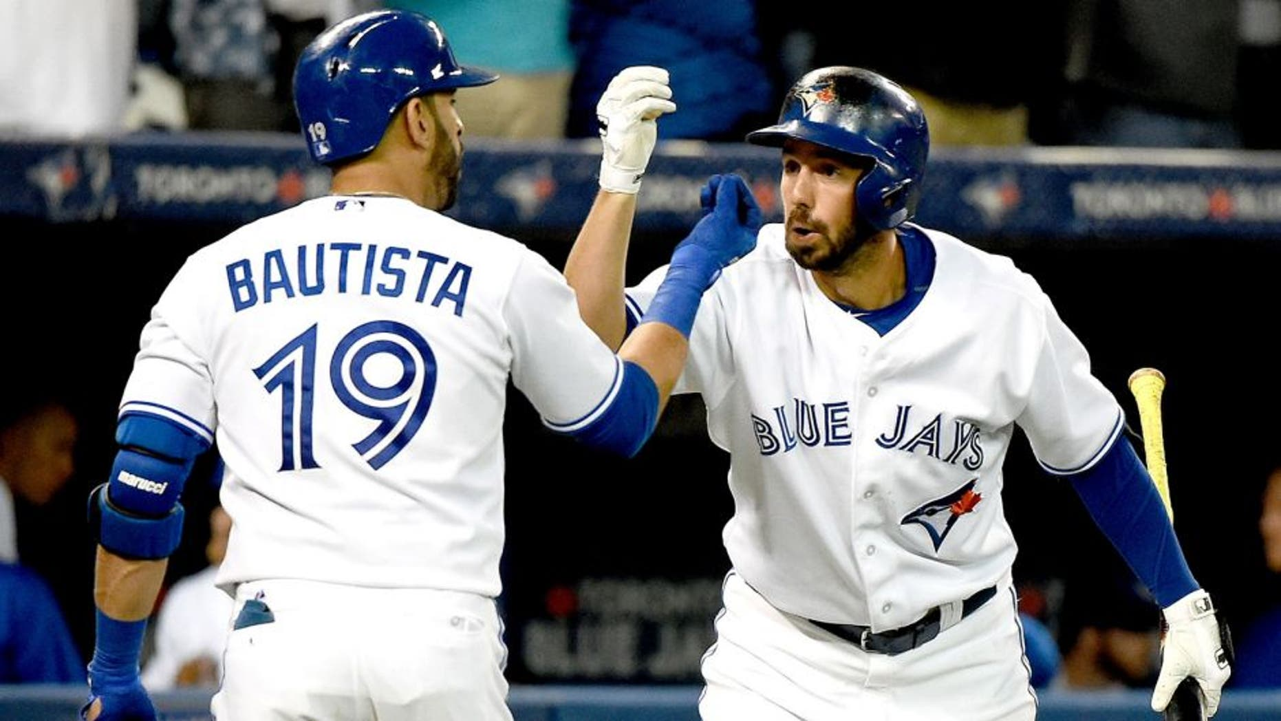 Aug 11, 2015; Toronto, Ontario, CAN; Toronto Blue Jays right fielder Jose Bautista (19) is greeted by designated hitter Chris Colabello (15) after hitting a home run against Oakland Athletics in the fifth inning at Rogers Centre. Mandatory Credit: Dan Hamilton-USA TODAY Sports