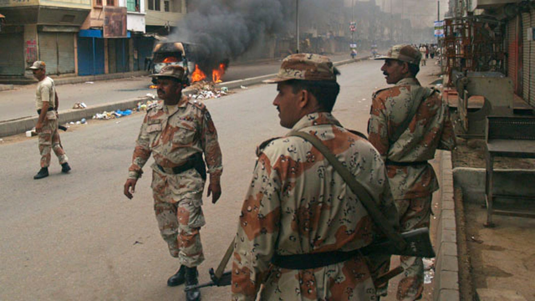 Aug. 3: Pakistani para military troops gather near a vehicle set on fire by an angry mob following the killing of a local leader of the Muttahida Quami Movement in Pakistan.
