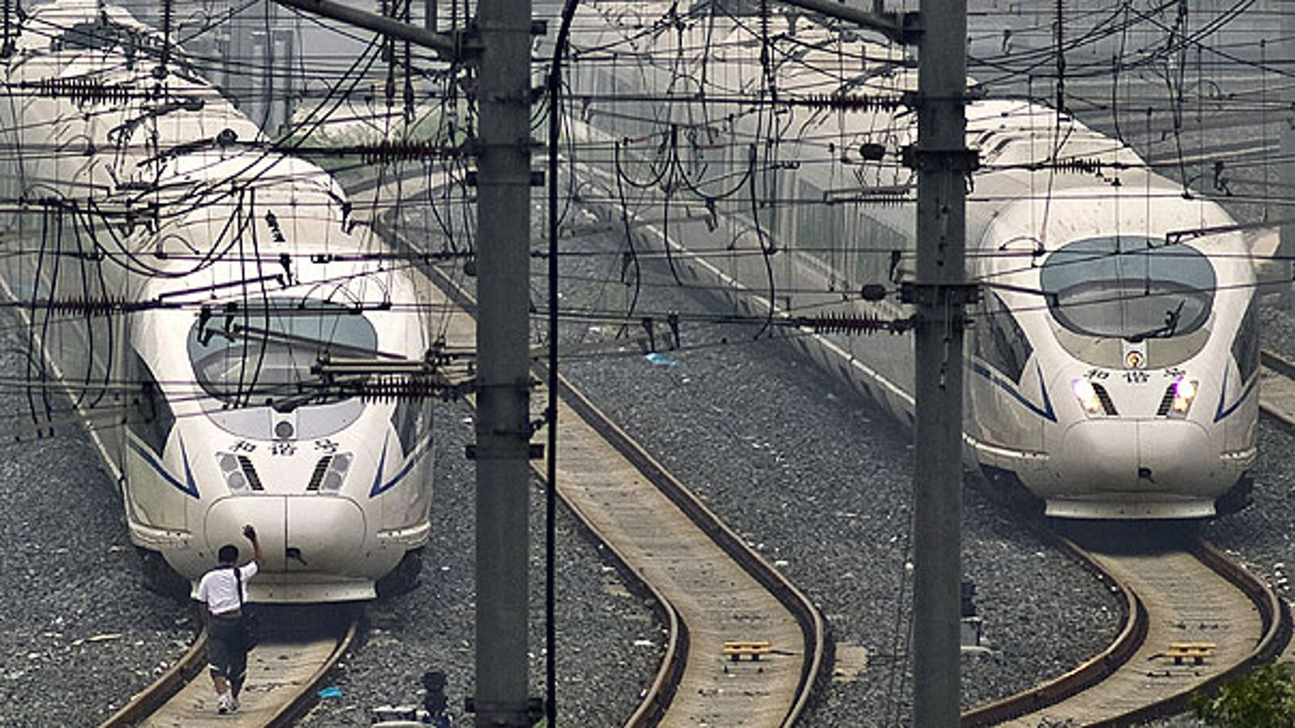 August 12: A train technician waves as he approaches CRH high-speed trains stopped on tracks at Beijing South Station in Beijing.
