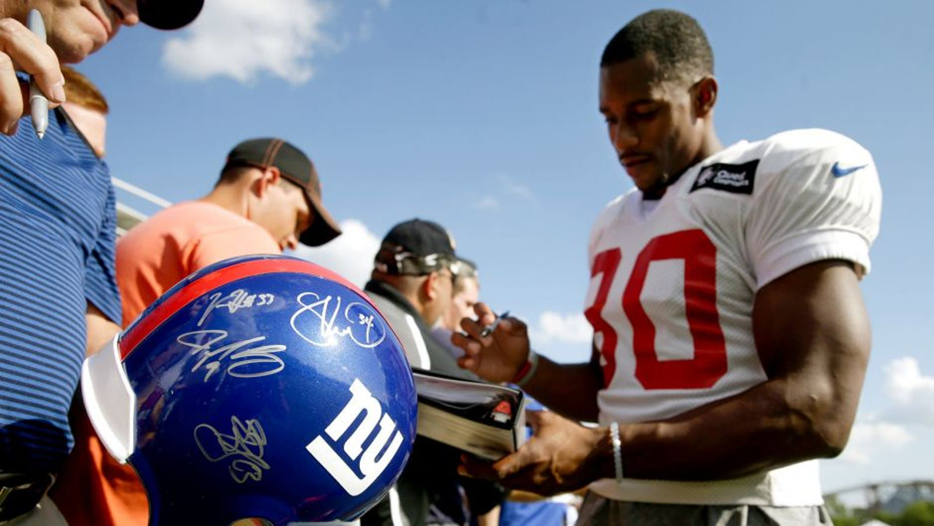 New York Giants wide receiver Victor Cruz, right, signs autographs after the Giants' joint NFL football training camp with the Cincinnati Bengals, Tuesday, Aug. 11, 2015, in Cincinnati. (AP Photo/John Minchillo)