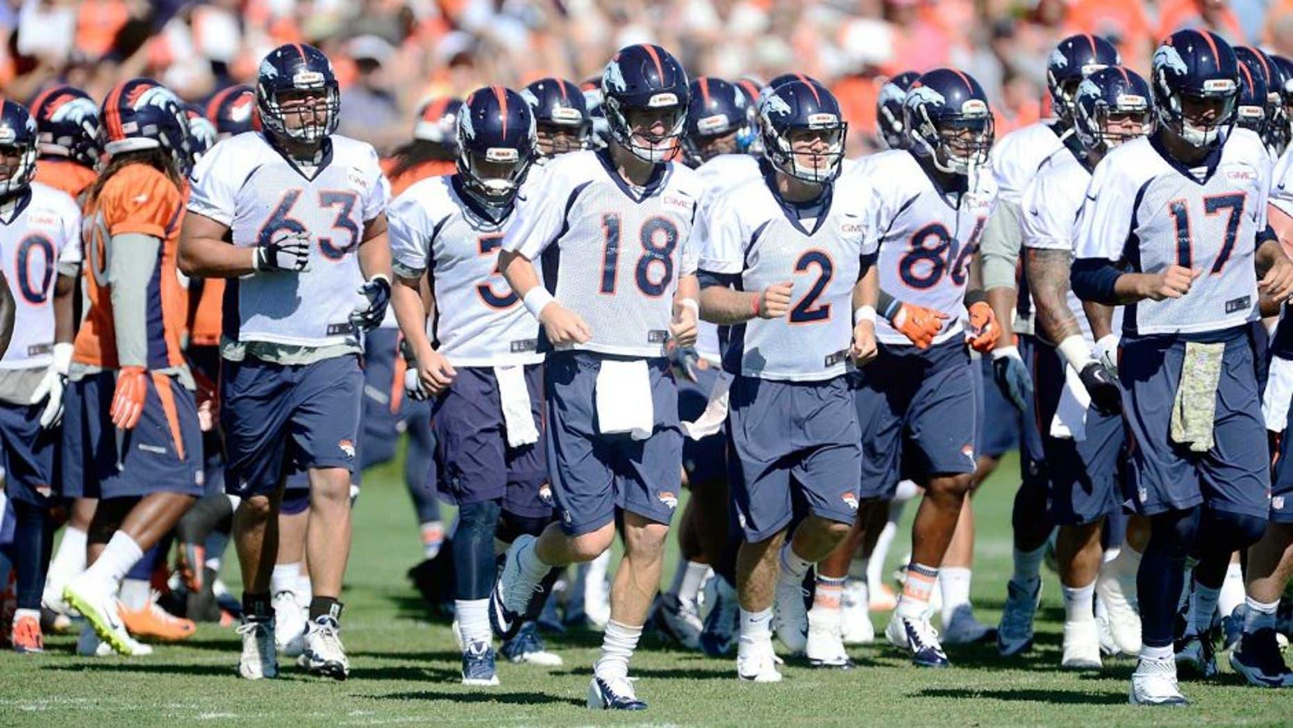 Aug 12, 2015; Englewood, CO, USA; Denver Broncos quarterback Peyton Manning (18), guard Ben Garland (63), quarterback Zac Dysert (2) and quarterback Brock Osweiler (17) warm up during training camp activities at the UCHealth Training Center. Mandatory Credit: Ron Chenoy-USA TODAY Sports