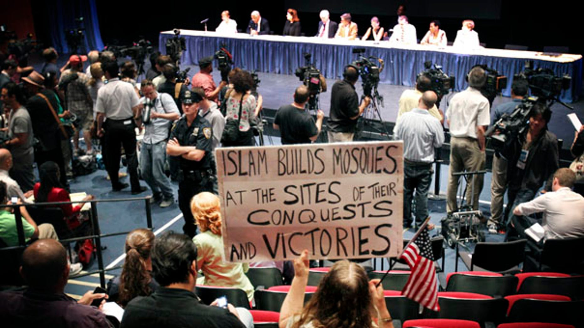 Aug. 3: A protester holds up a sign opposing the construction of a mosque and Islamic center near New York's ground zero during a hearing of the Landmarks Preservation Commission.