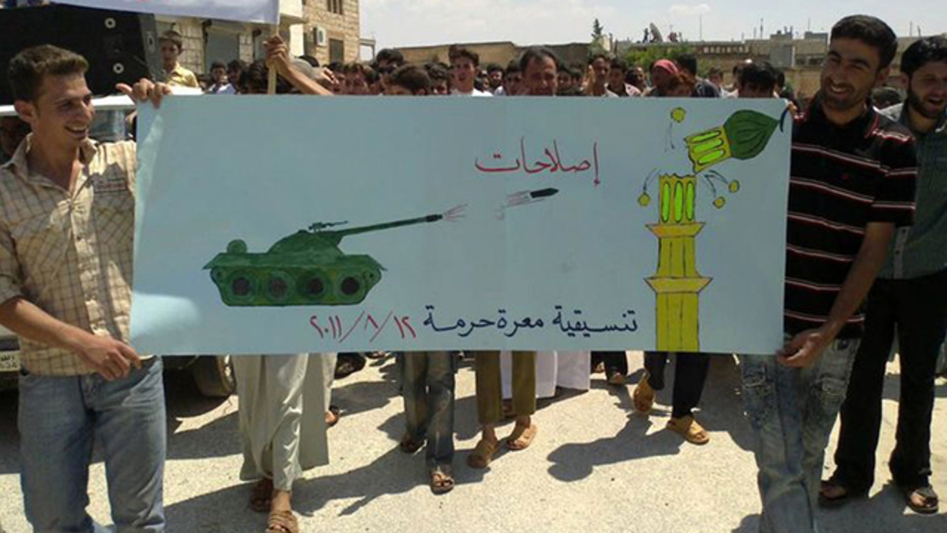 Aug. 12: In this citizen journalism image made on a mobile phone and provided by Shaam News Network, anti-Syrian President Bashar Assad protesters hold up a banner depicting a Syrian tank shelling a mosque during a demonstration against the Syrian regime, at Maarat Harma village, in Edlib province, northen Syria.