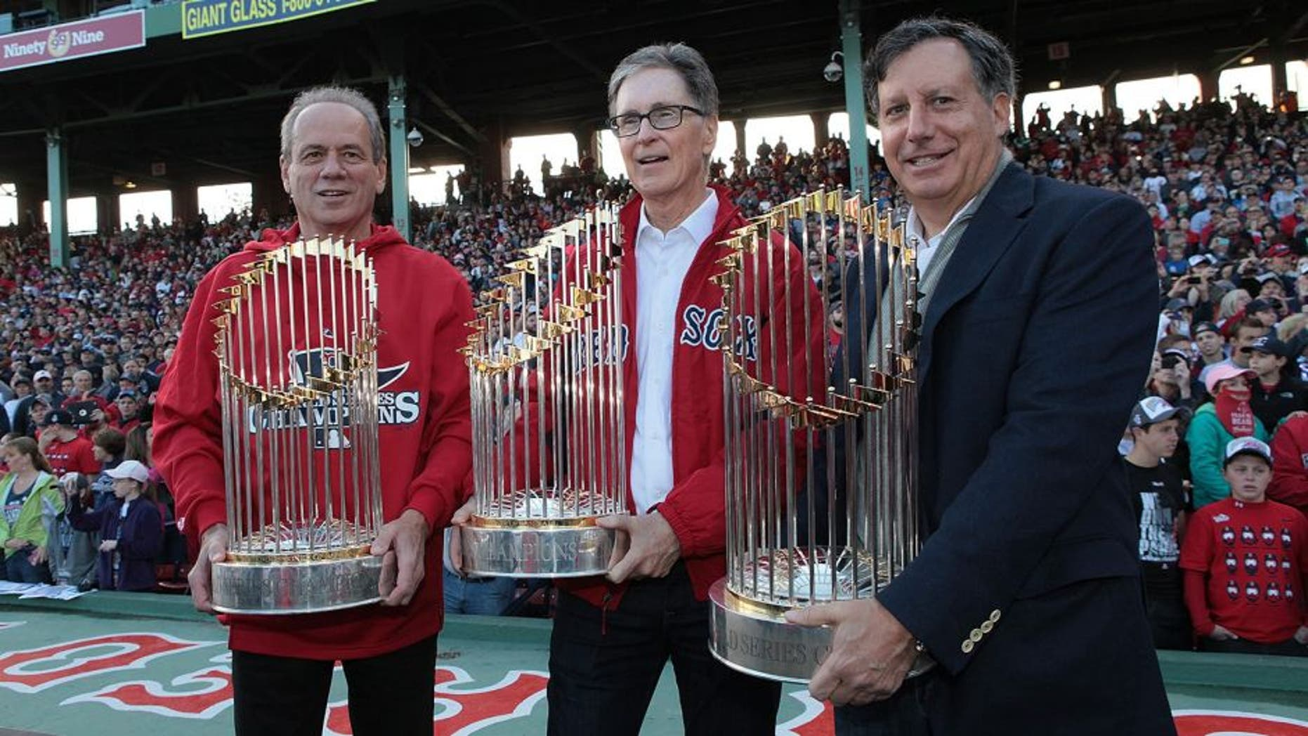 BOSTON, MA - NOVEMBER 2: President and CEO of the Boston Red Sox Larry Lucchino, (left), Red Sox principal own John Henry (center), and Red Sox chairmanTom Werner show off the World Series trophies to the crowd at Fenway Park before the Red Sox players board the duck boats for the World Series victory parade for the Boston Red Sox on November 2, 2013 in Boston, Massachusetts. (Photo by Gail Oskin/Getty Images)