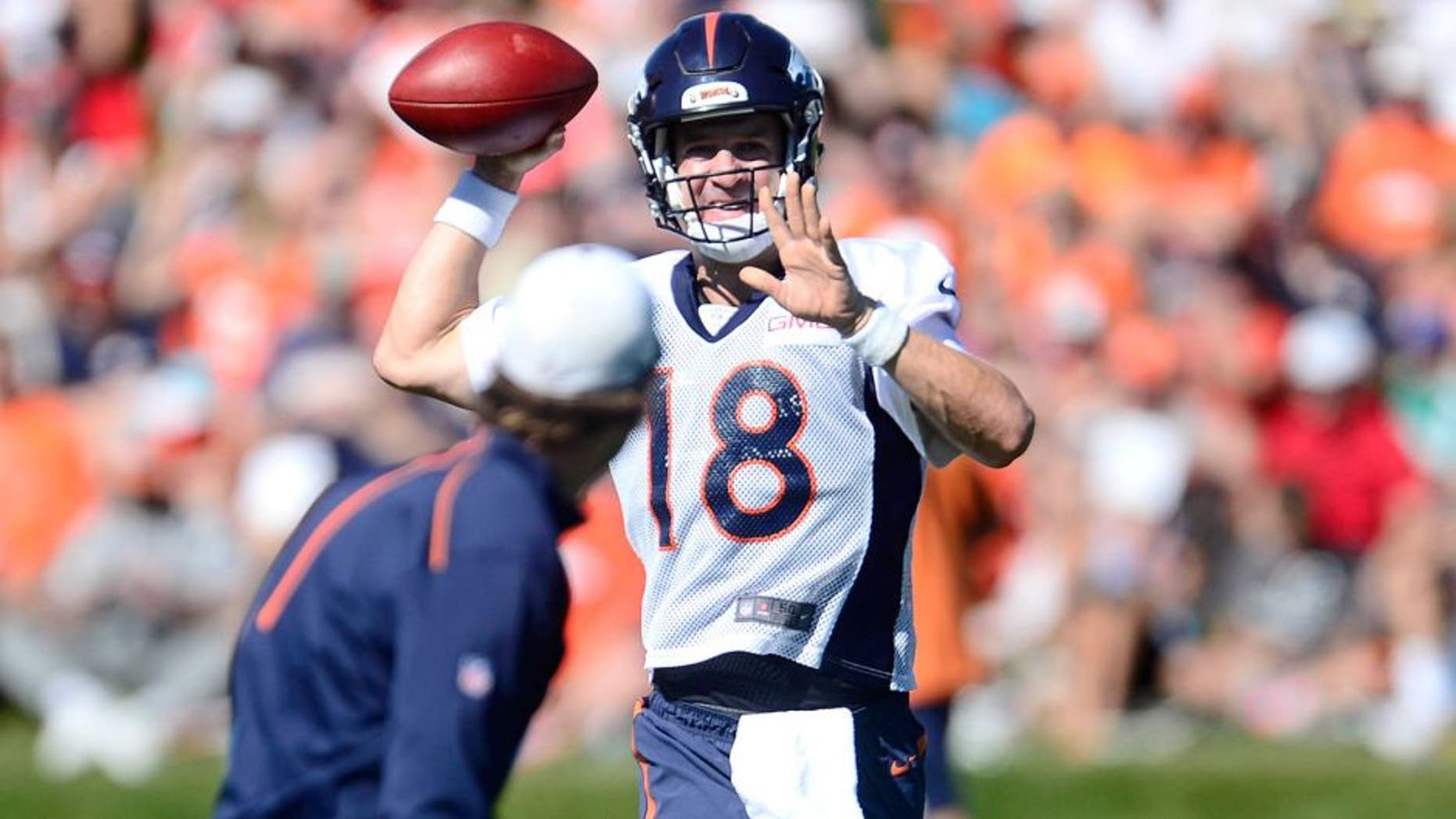 Aug 12, 2015; Englewood, CO, USA; Denver Broncos quarterback Peyton Manning (18) warms up with passing drills during training camp activities at the UCHealth Training Center. Mandatory Credit: Ron Chenoy-USA TODAY Sports