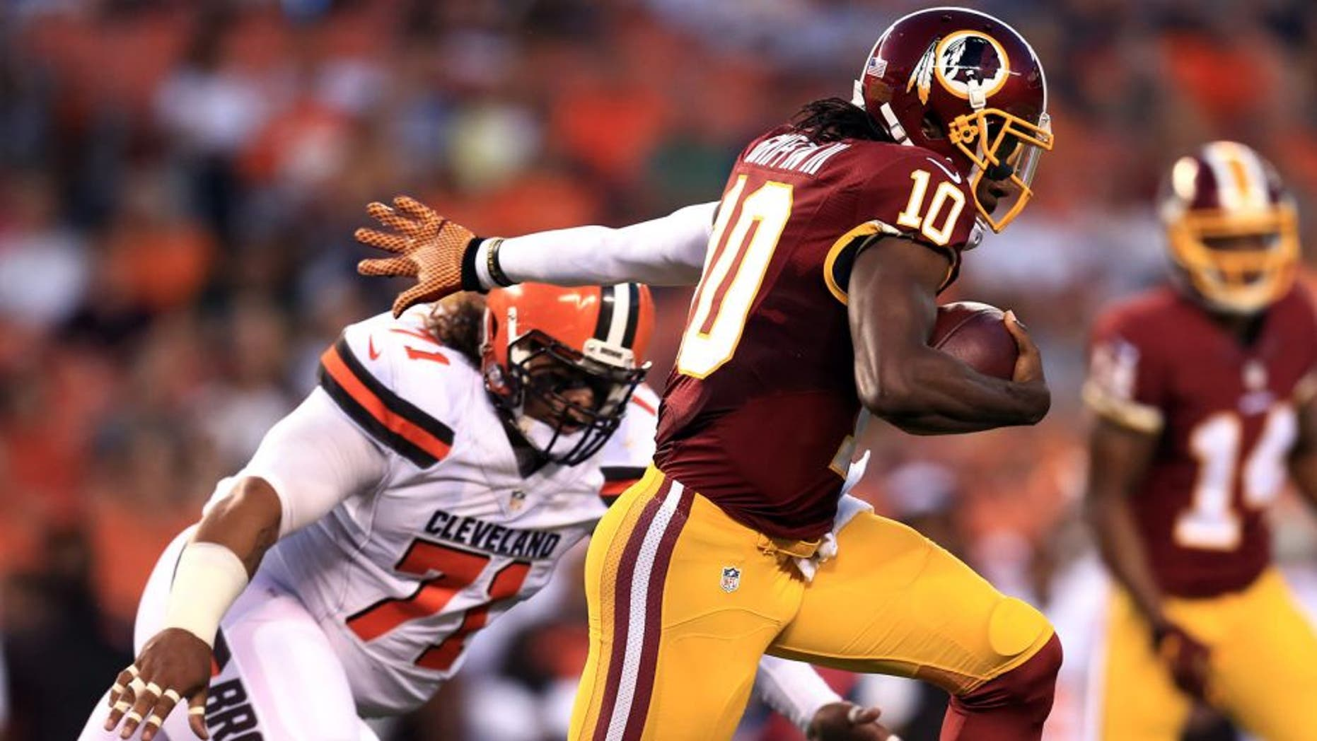 Aug 13, 2015; Cleveland, OH, USA; Washington Redskins quarterback Robert Griffin III (10) runs the ball during the first quarter of preseason NFL football game against the Cleveland Browns at FirstEnergy Stadium. Mandatory Credit: Andrew Weber-USA TODAY Sports