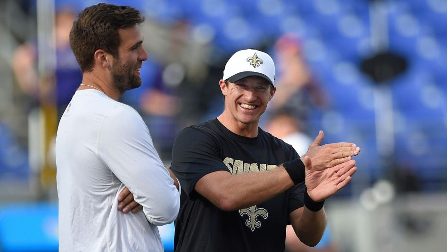 Baltimore Ravens quarterback Joe Flacco, left, talks with New Orleans Saints quarterback Drew Brees before an NFL preseason football game in Baltimore, Thursday, Aug. 13, 2015. (AP Photo/Nick Wass)
