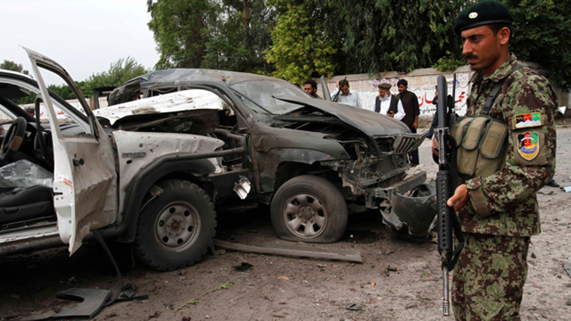 Aug. 2, 2010: Afghans gather at the scene of an attack on a presidential adviser in Jalalabad, east of Kabul, Afghanistan. Militants attacked the second government official in the east on the same day.