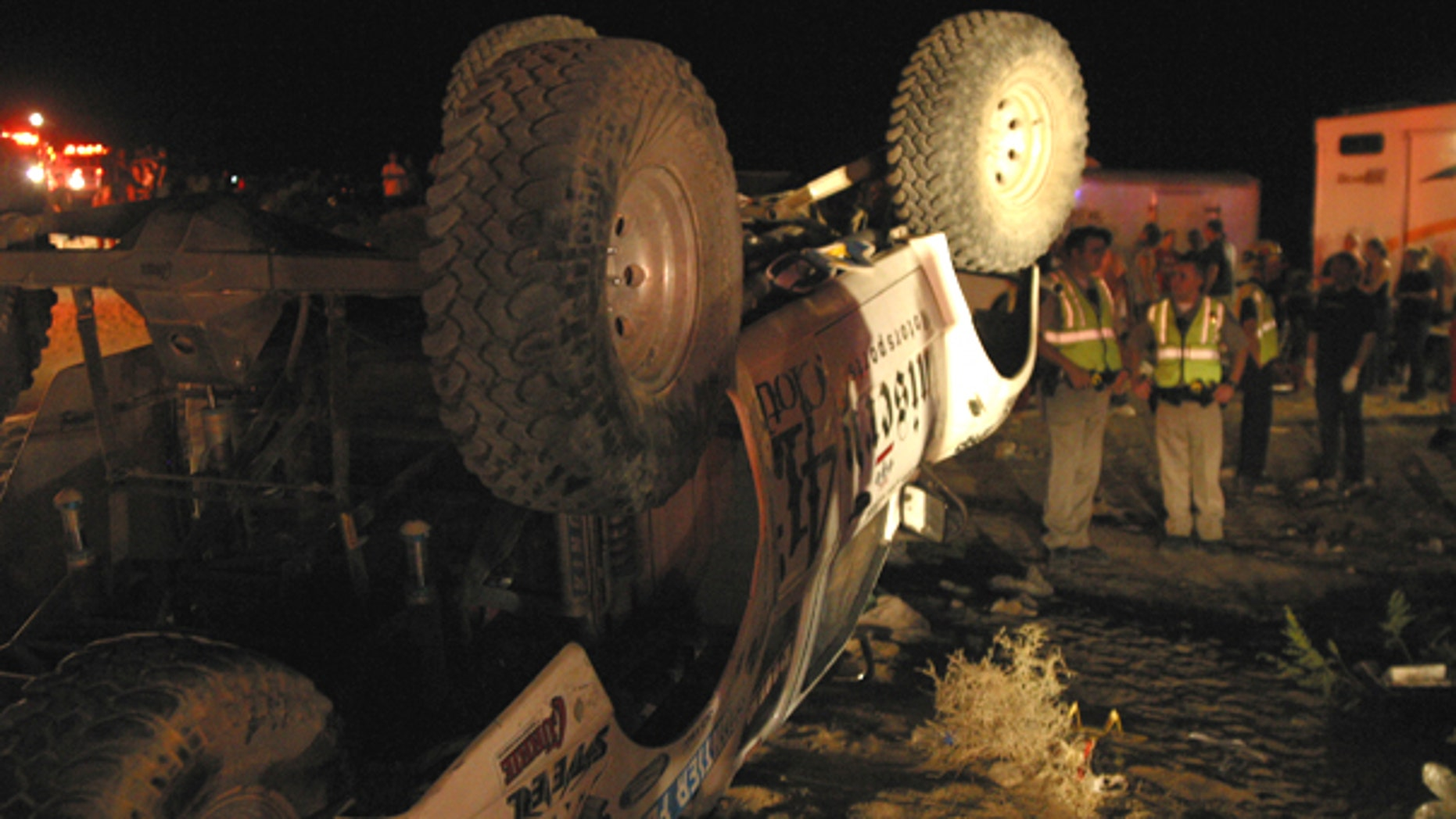 Aug. 14: Emergency workers look at an off-highway vehicle that lost control and barreled into a crowd of spectators at an off-road race called the California 200.
