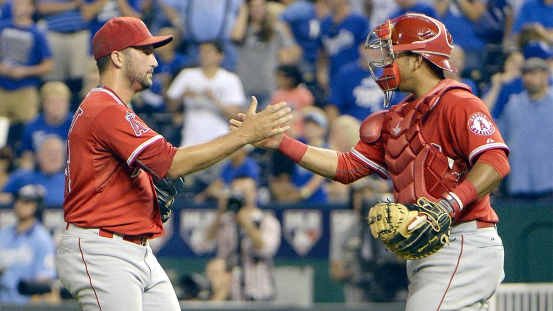 Aug 13, 2015; Kansas City, MO, USA; Los Angeles Angels relief pitcher Huston Street (16) celebrates with catcher Carlos Perez (58) after the game against the Kansas City Royals at Kauffman Stadium. The Angels won the game 7-6. Mandatory Credit: John Rieger-USA TODAY Sports