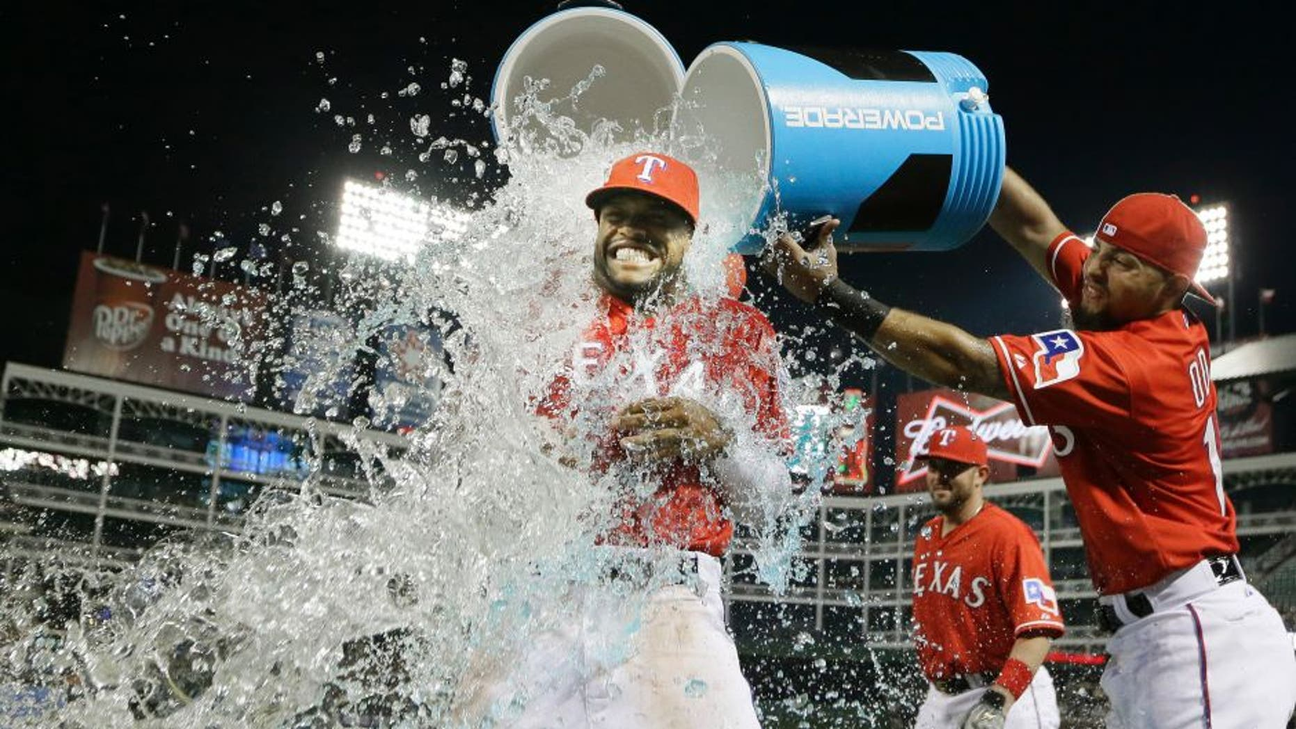 Texas Rangers Delino DeShields, left, gets doused with the drink cooler by teammate Rougned Odor after a baseball game against the Tampa Bay Rays in Arlington, Texas, Friday, Aug. 14, 2015. The Rangers won 5-3. (AP Photo/LM Otero)