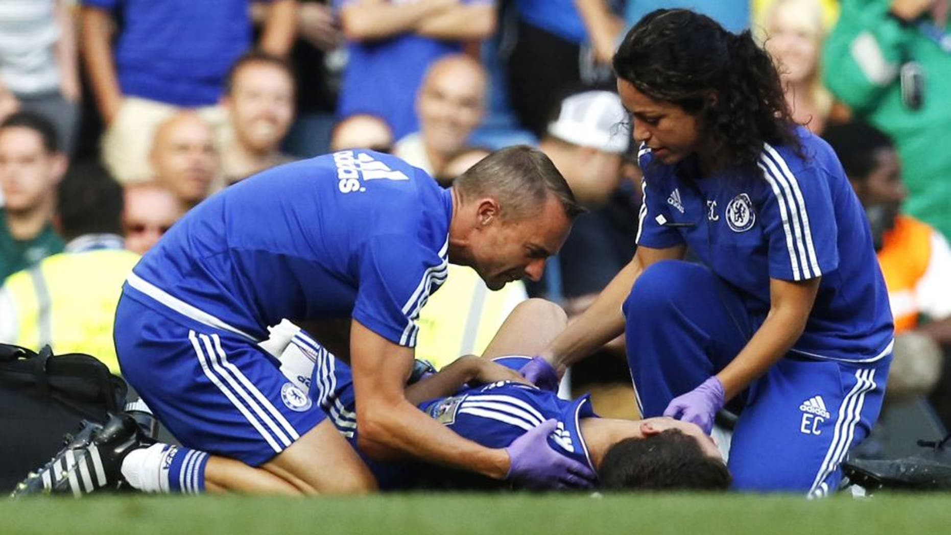 """Chelsea doctor (R) Eva Carneiro and head physio Jon Fearn (L) treat Chelsea's Belgian midfielder Eden Hazard late on during the English Premier League football match between Chelsea and Swansea City at Stamford Bridge in London on August 8, 2015. Chelsea have sidelined team doctor Eva Carneiro from match-day duties after she fell foul of manager Jose Mourinho, according to British media reports on August 11, 2015. Mourinho criticised Carneiro after she ran on the pitch to treat Eden Hazard in stoppage time of Chelsea's 2-2 draw at home to Swansea City on August 8, saying she did not """"understand the game"""". AFP PHOTO / IAN KINGTON RESTRICTED TO EDITORIAL USE. No use with unauthorized audio, video, data, fixture lists, club/league logos or 'live' services. Online in-match use limited to 75 images, no video emulation. No use in betting, games or single club/league/player publications. (Photo credit should read IAN KINGTON/AFP/Getty Images)"""