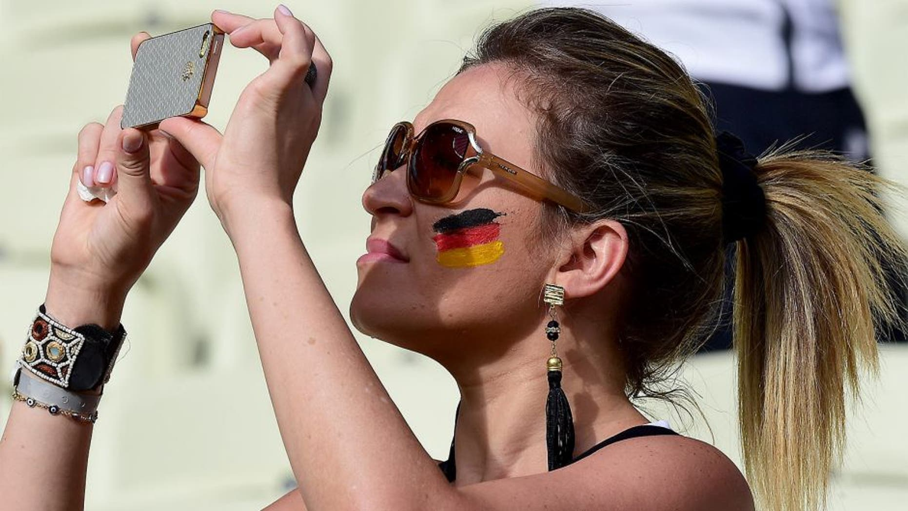 A German fan takes pictures with her phone before the start of the Group G football match between Germany and Ghana at the Castelao Stadium in Fortaleza during the 2014 FIFA World Cup on June 21, 2014. AFP PHOTO / JAVIER SORIANO