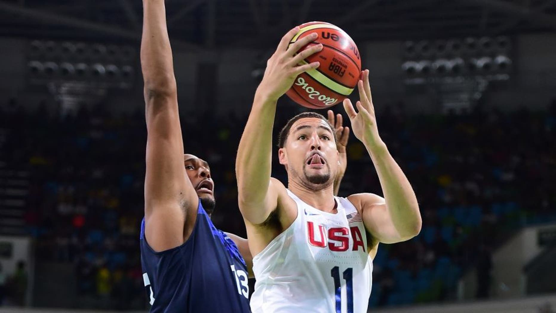 RIO DE JANEIRO, BRAZIL - AUGUST 14: Klay Thompson #11 of United States shoots past Boris Diaw #13 of France during a Men's Preliminary Round Group A game between the United States and France on Day 9 of the Rio 2016 Olympic Games at Carioca Arena 1 on August 14, 2016 in Rio de Janeiro, Brazil. (Photo by Harry How/Getty Images)