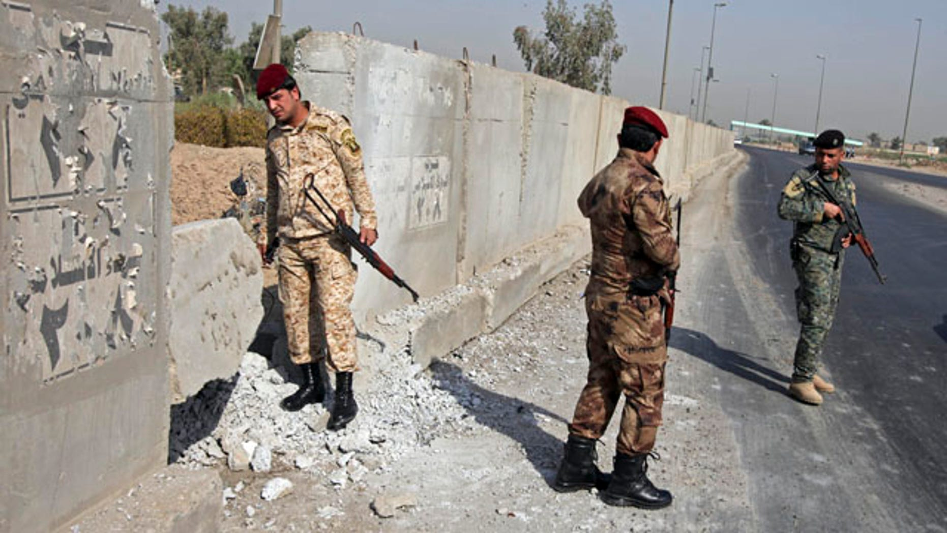 Aug. 15: Iraqi army soldiers secure the scene of a roadside bomb attack in Baghdad, Iraq.